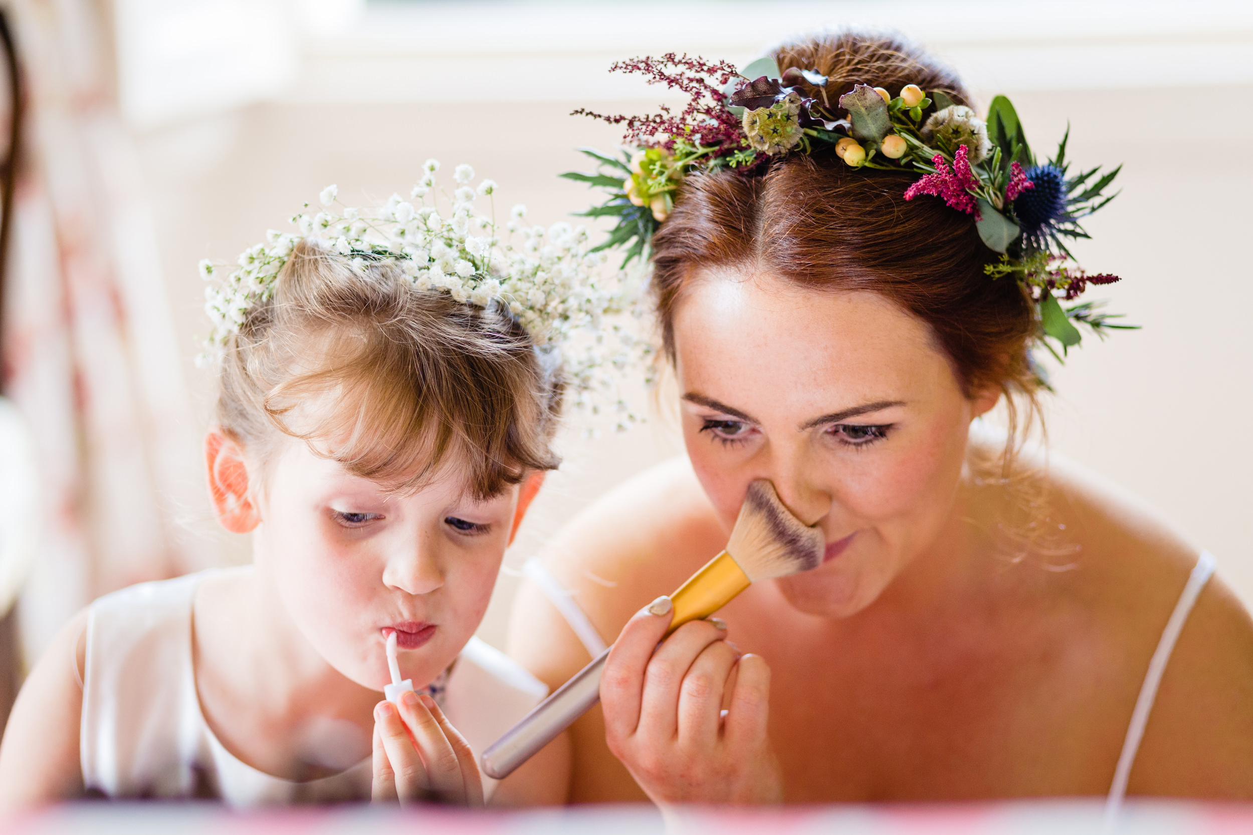 bride and flower girl doing makeup. scotland wedding photography by emma and rich.