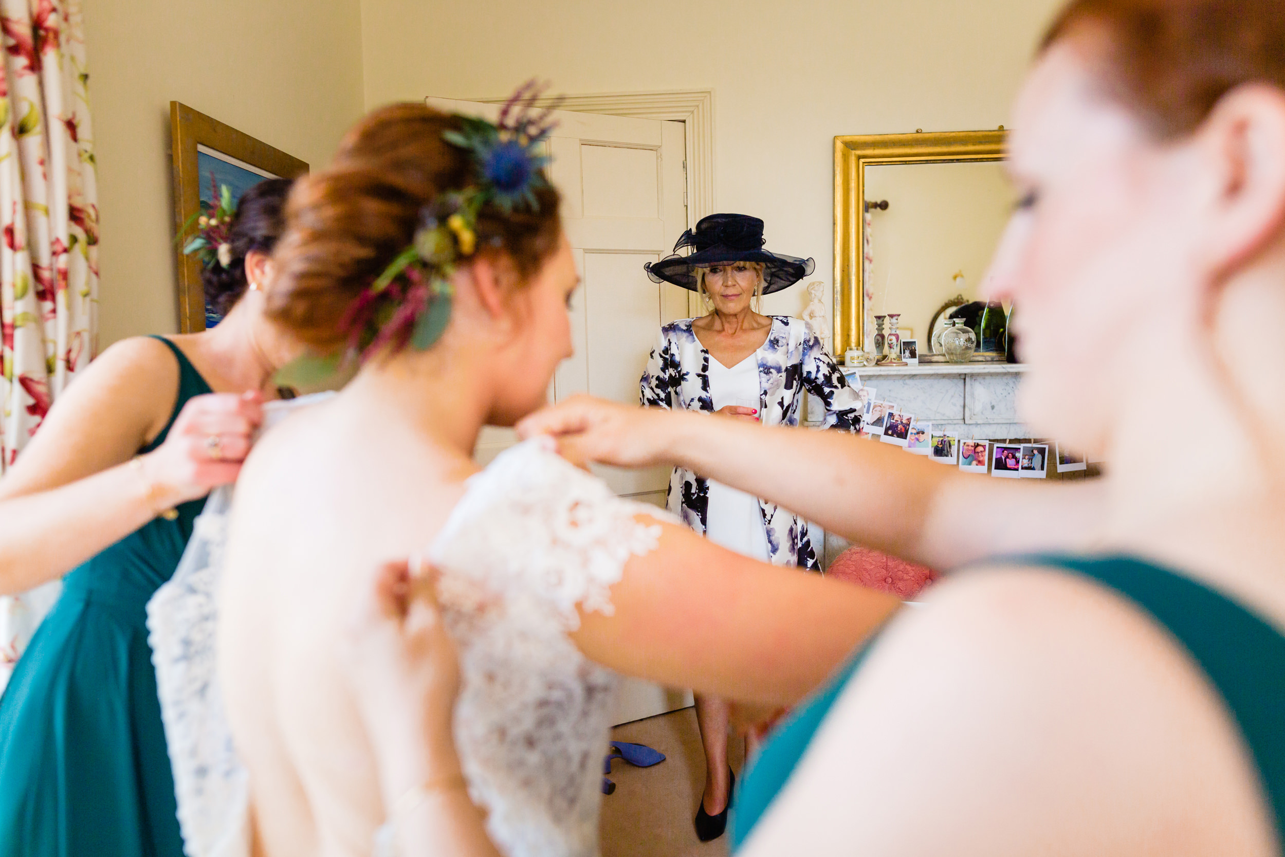 mother of the bride watches the dress being put on. scotland wedding photography by emma and rich.