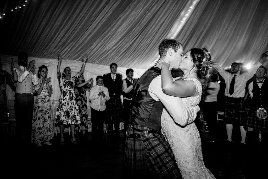 bride and groom kiss on the dancefloor surrounded by their friends. scotland wedding photography by emma and rich.