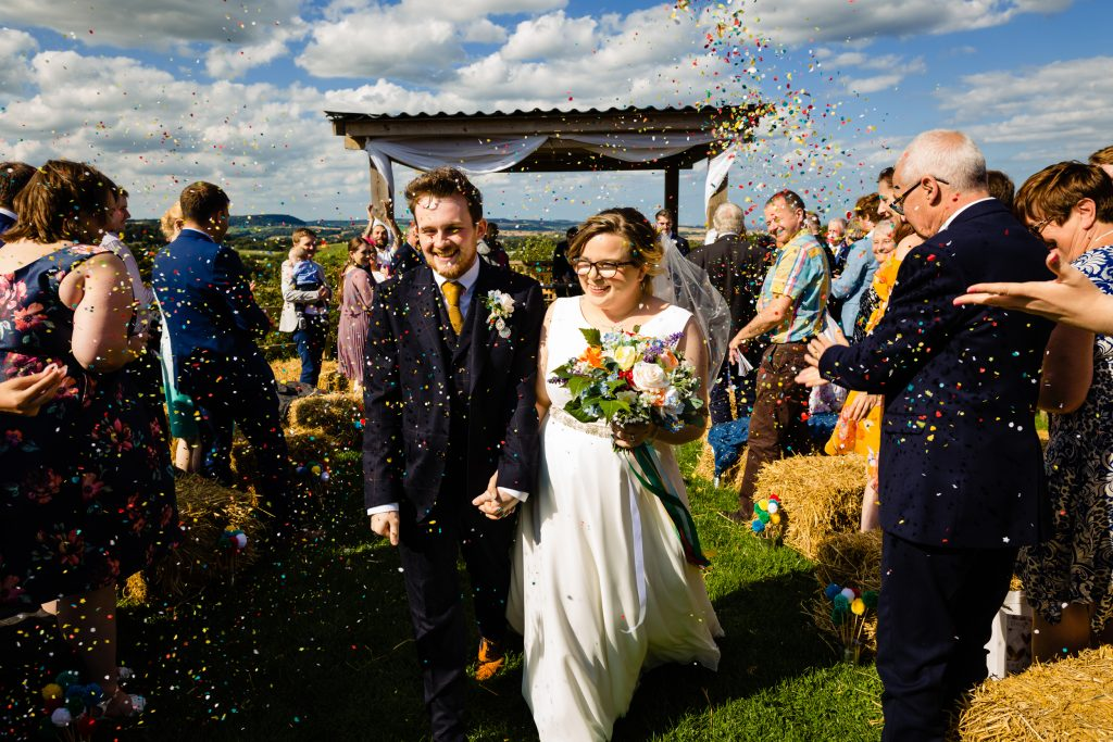 bride and groom walk down the aisle and get pelted with confetti. colourful outdoor wedding photography by emma and rich.