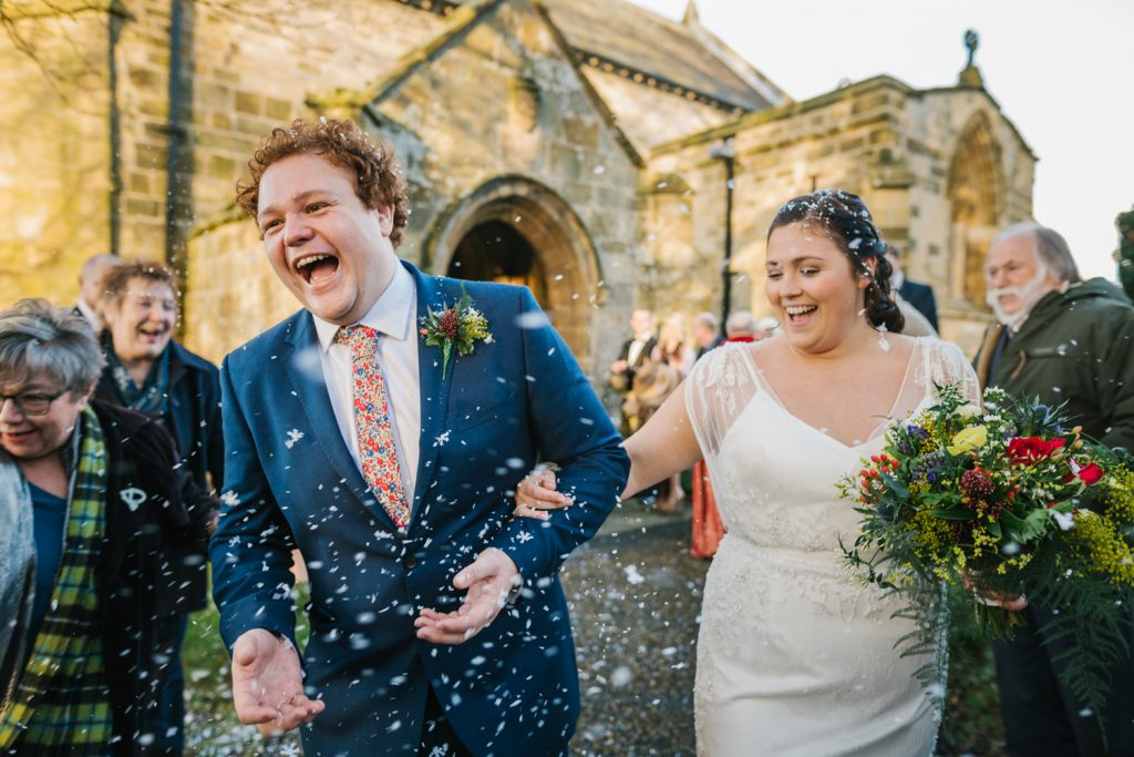 a bride and groom laughing as they exit the church ceremony and are showered in confetti. intimate country wedding photography by emma and rich.