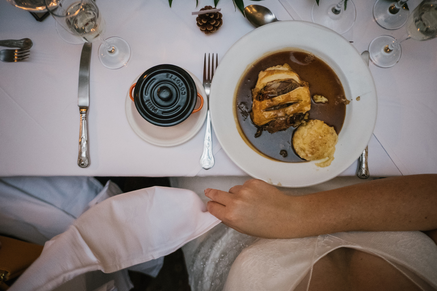 a birds eye view of a wedding meal served at wrangham house, a very posh pie and mash. the photo is taken from above the bride and you can see her starting to place the napkin on her lap. intimate country wedding photography by emma and rich.