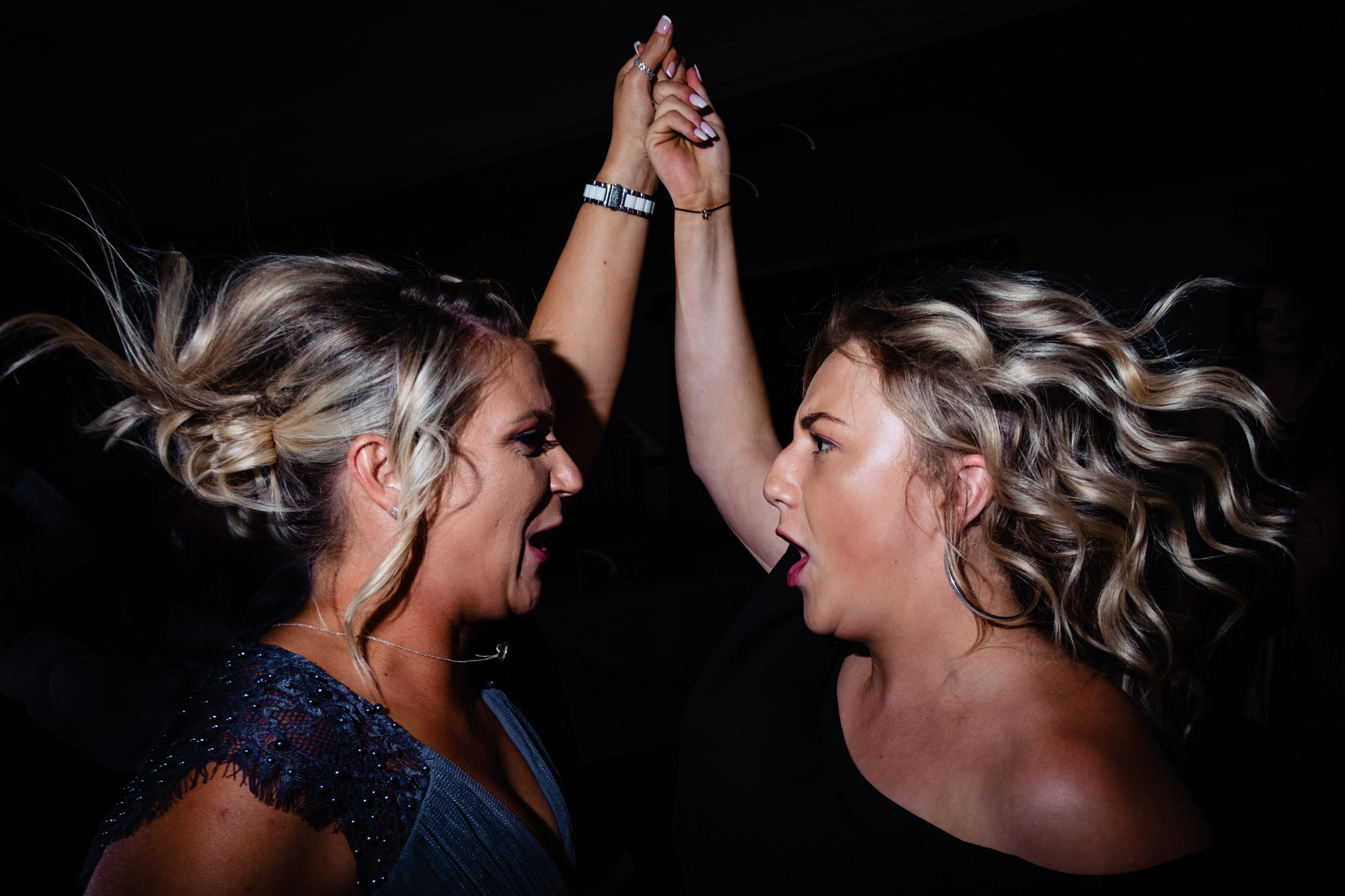 two ladies jumping around on the dancefloor. huntsman inn wedding photography by emma and rich.