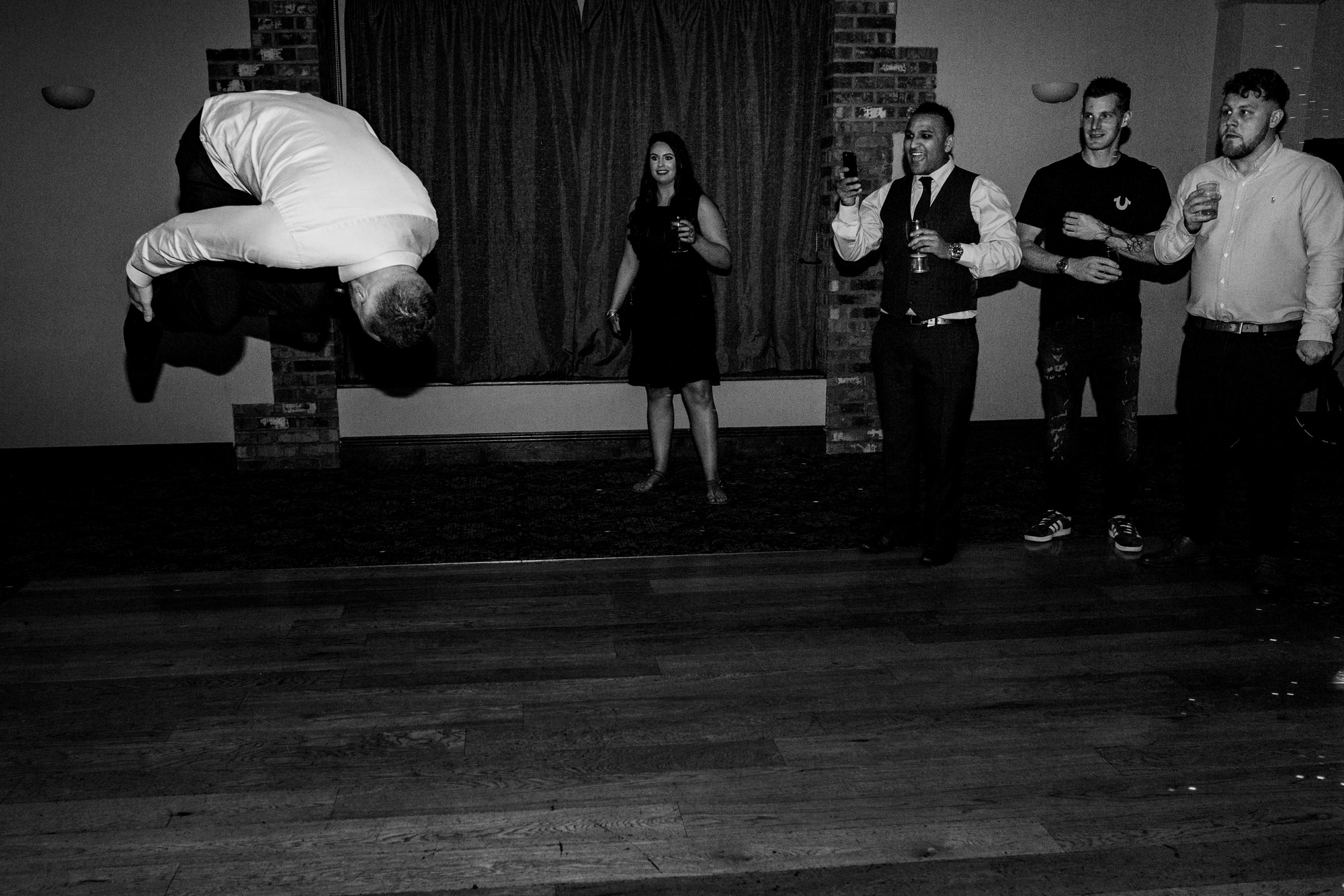 people look on as man does a flip on the dancefloor. huntsman inn wedding photography by emma and rich.