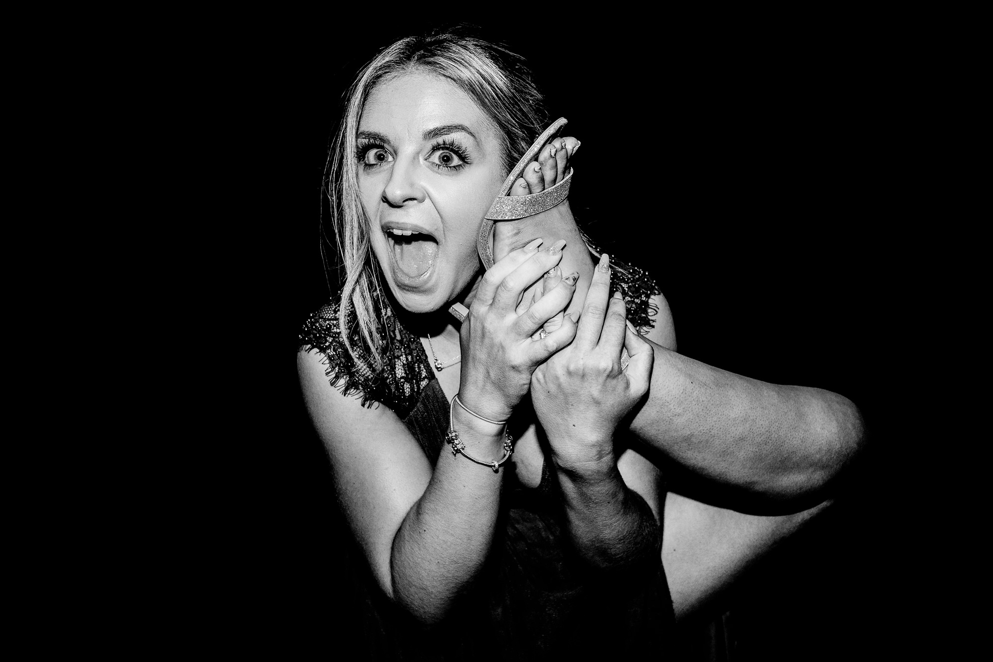bridesmaid trying to use her own foot as a phone. huntsman inn wedding photography by emma and rich.