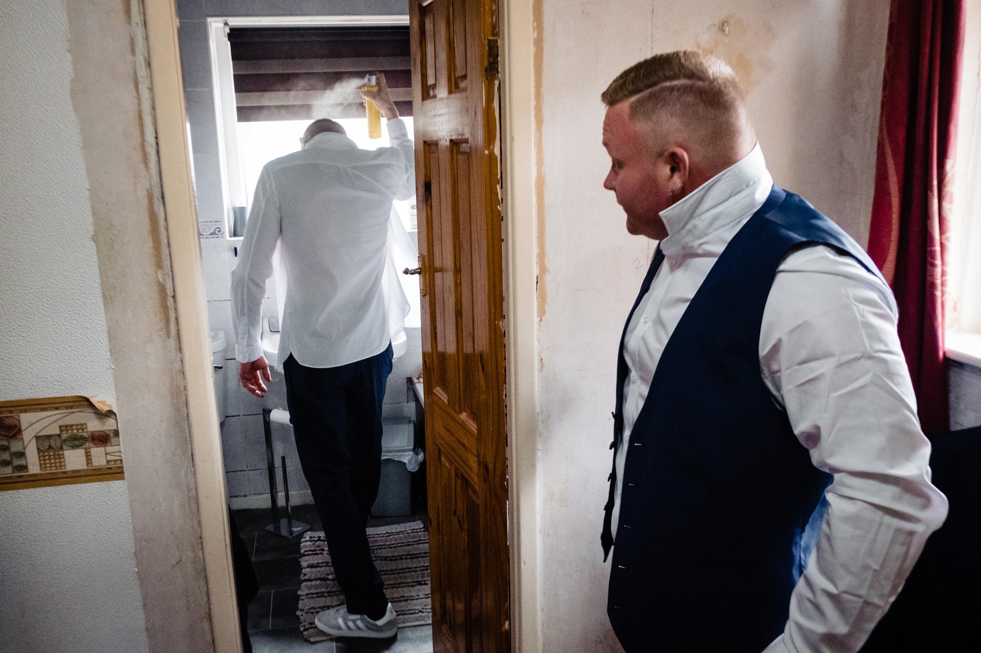 groom using hairspray in the bathroom as an usher looks on.