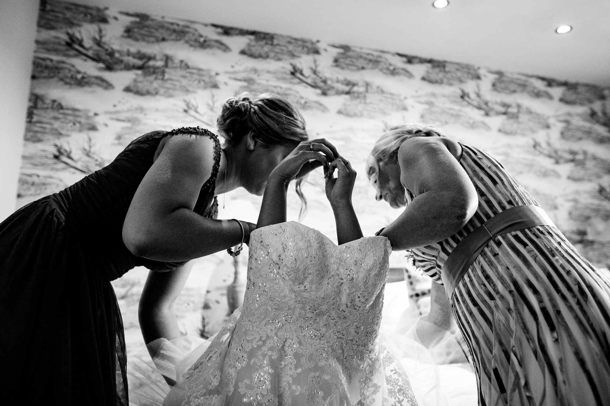 a bride being helped into her wedding dress. you can just see her hands poking out of the top. huntsman inn wedding photography by emma and rich.