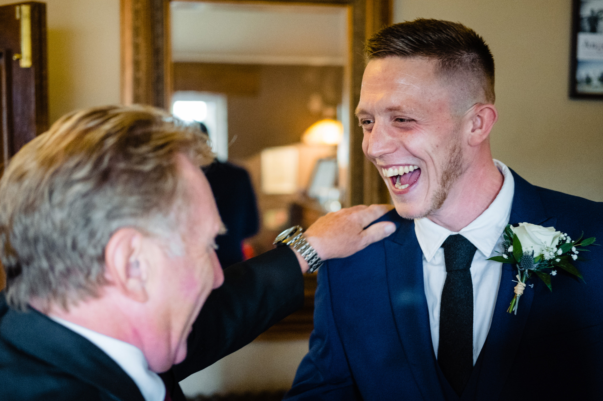 a grinning groom being congratulated by a guest.