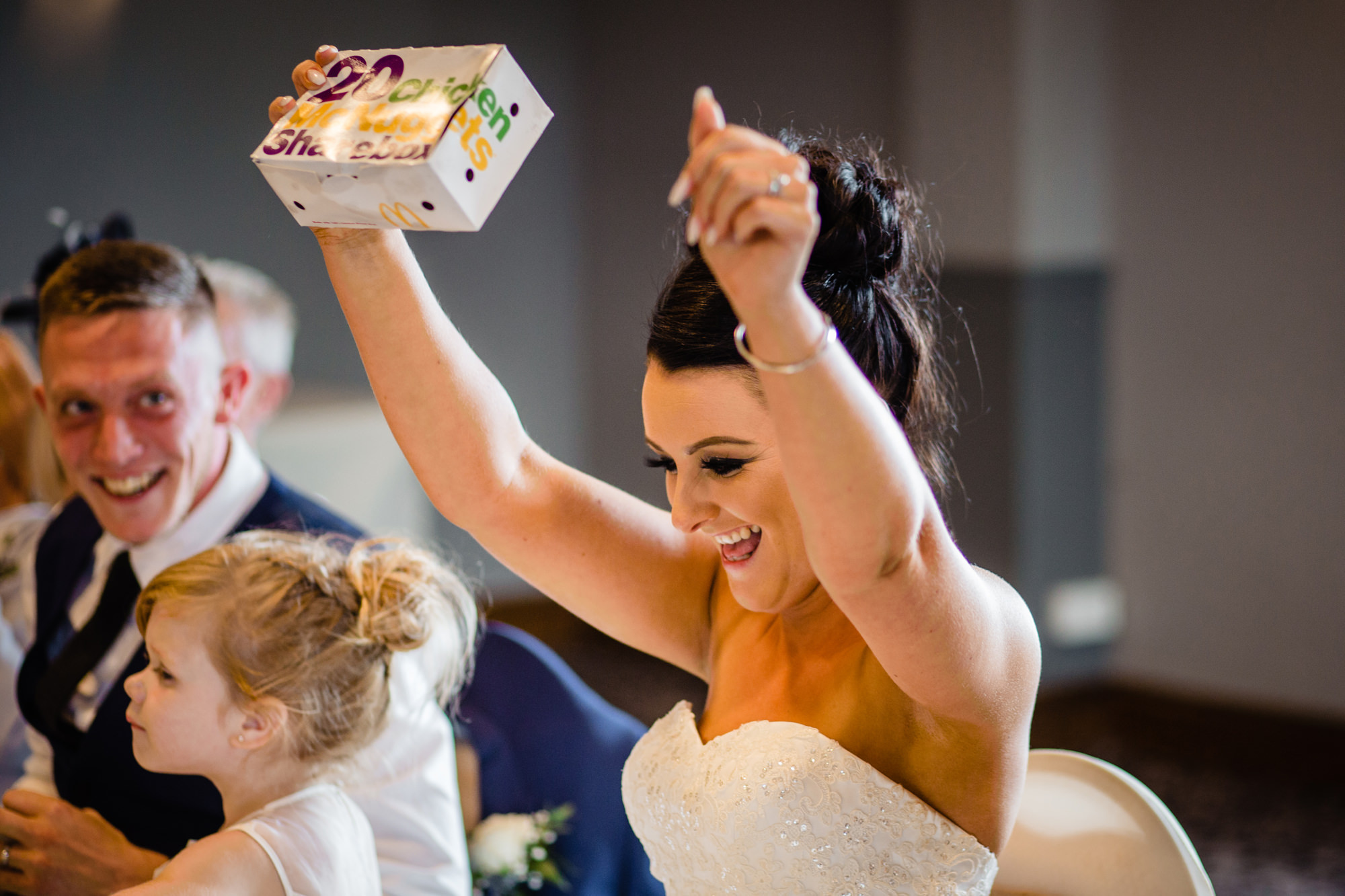 bride celebrates as she receives a box of chicken mcnuggets as a gift. huntsman inn wedding photography by emma and rich.