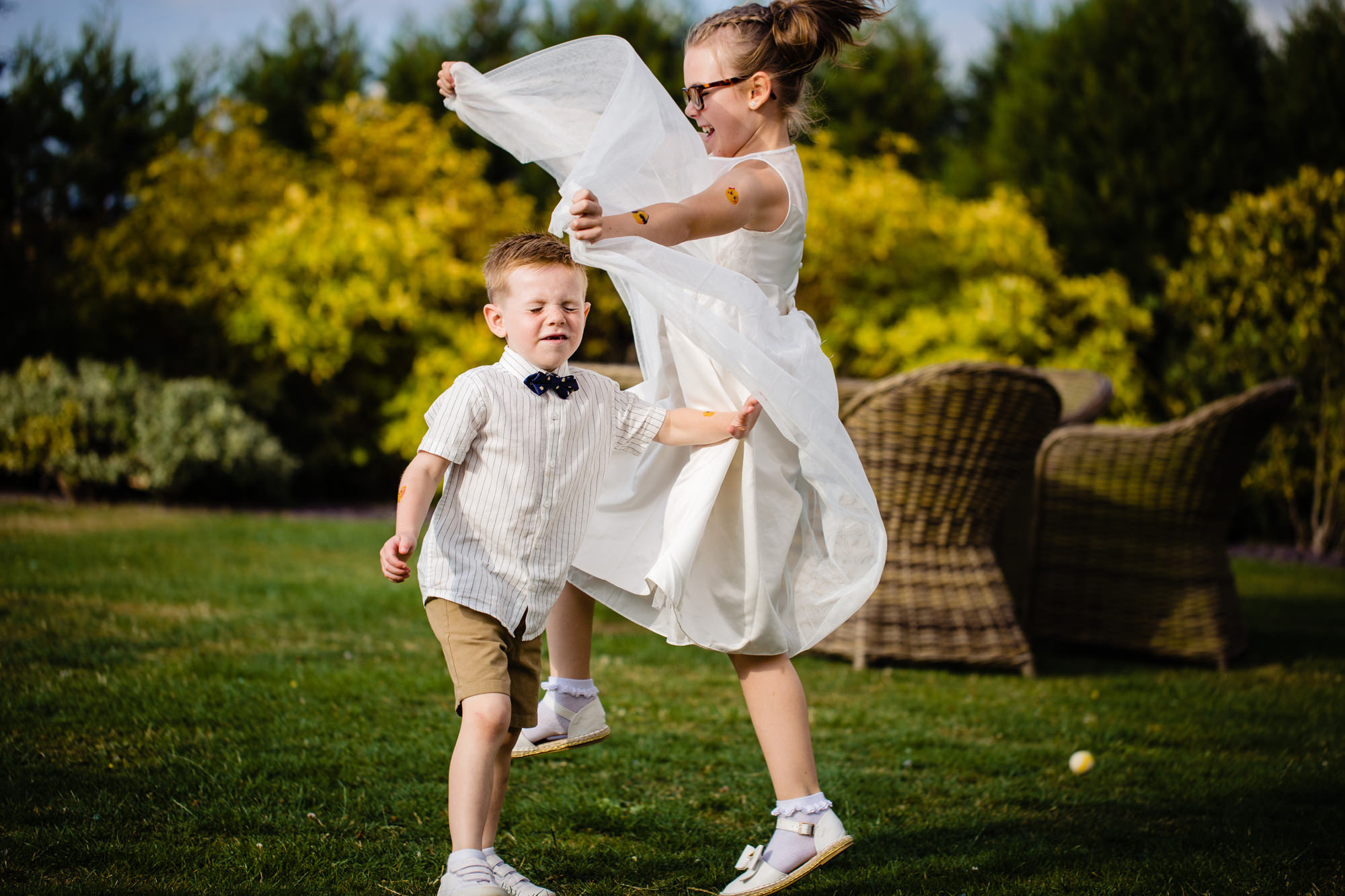 children playing on the lawn at a wedding.