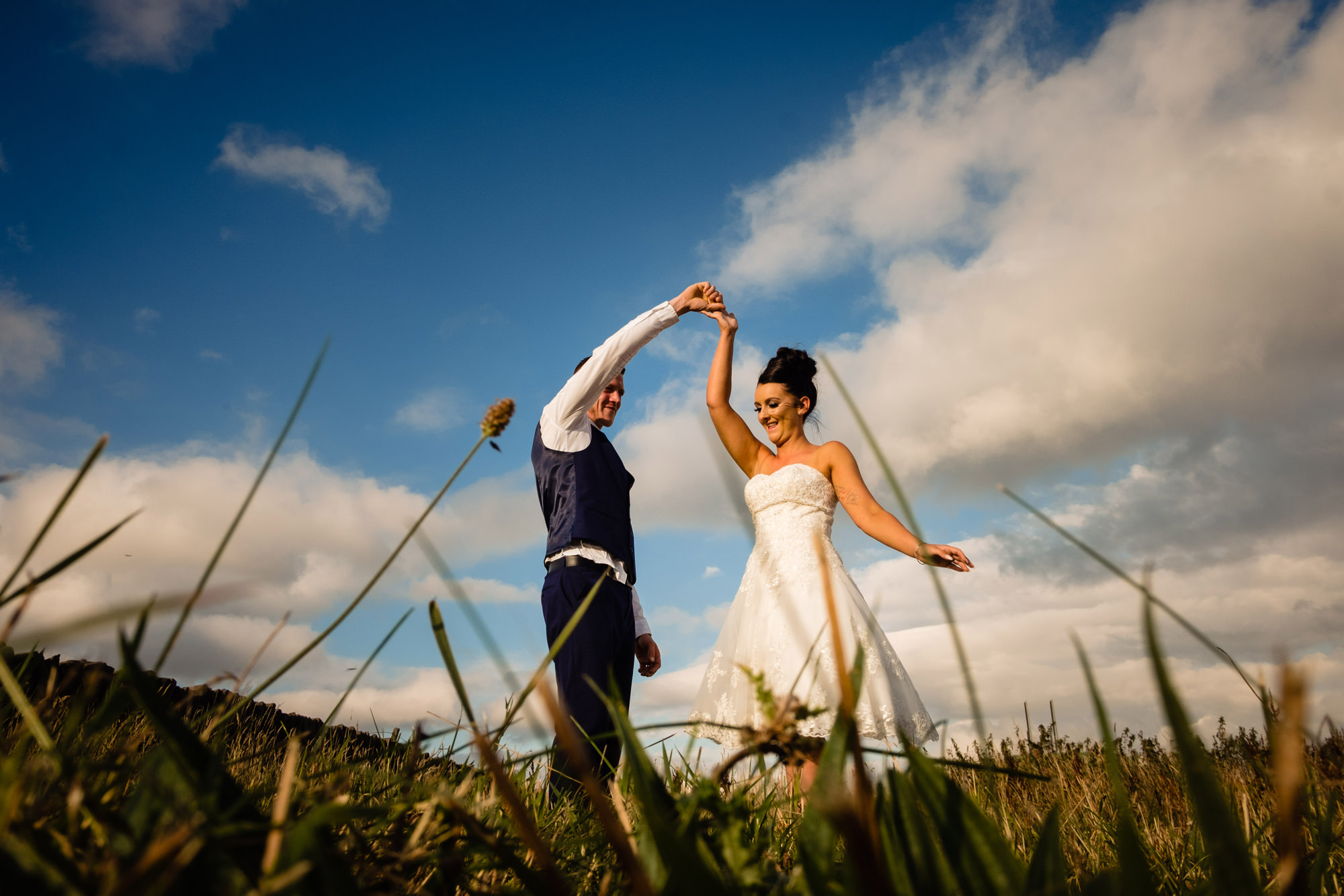 a bride and groom dancing in the countryside. huntsman inn wedding photography by emma and rich.