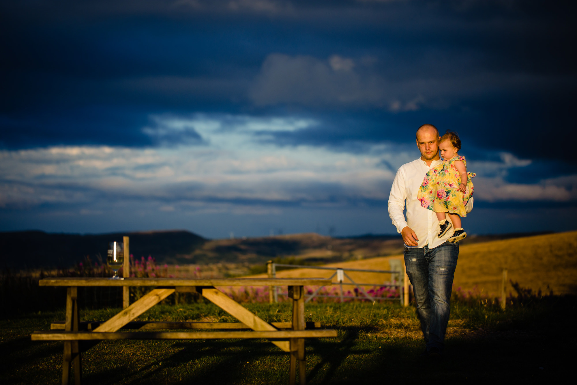 wedding guest carrying child in garden. huntsman inn wedding photography by emma and rich.