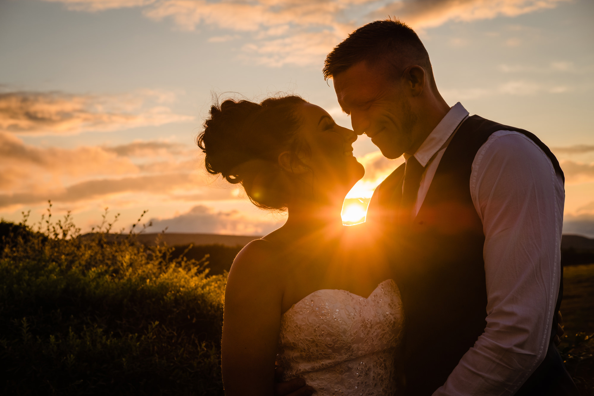 a newly married couple hug as the setting sun peaks through between them. huntsman inn wedding photography by emma and rich.