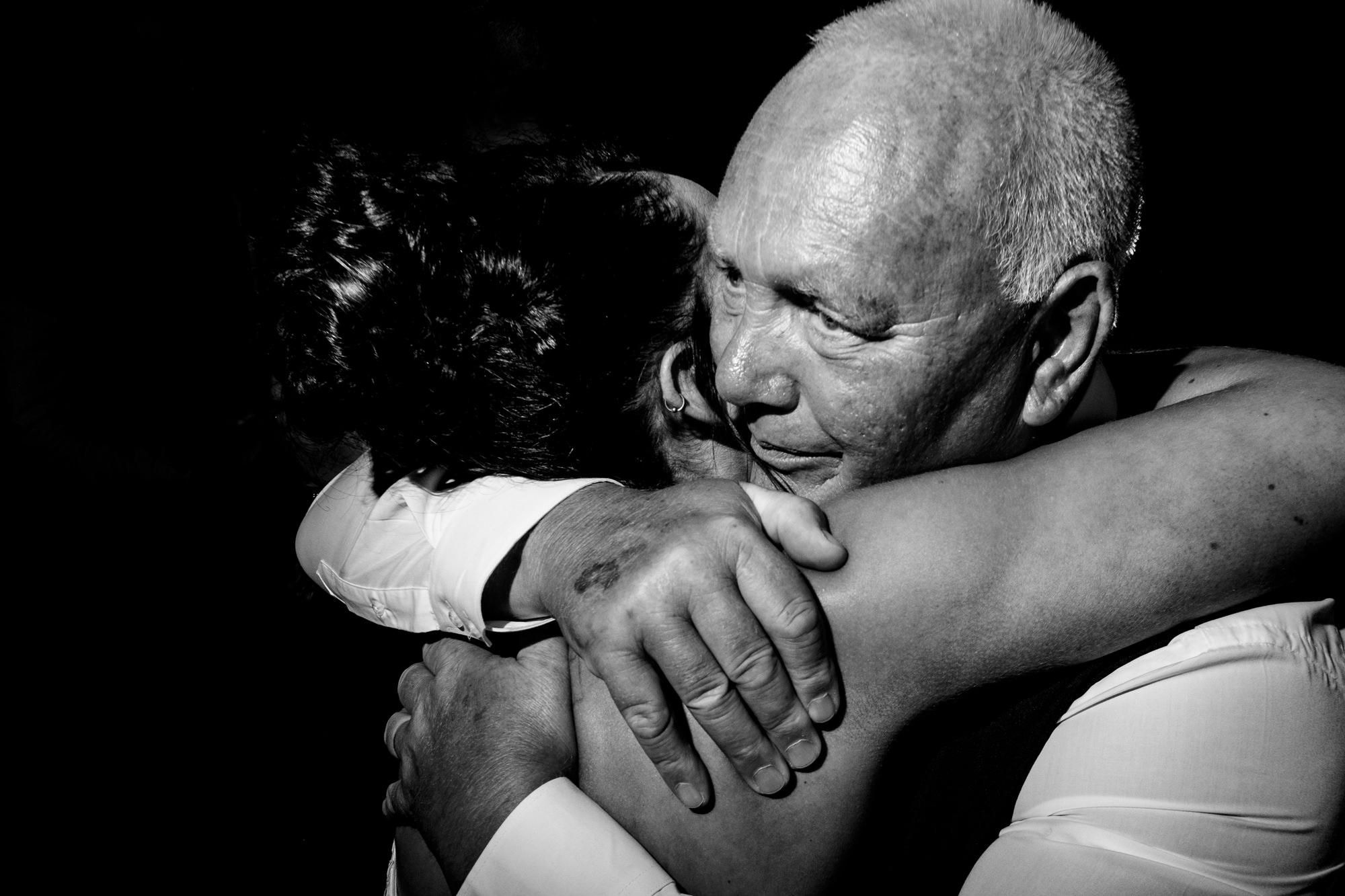 guest hugging bride on the dancefloor.