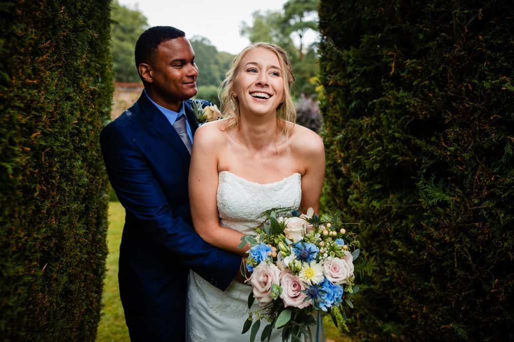 newlyweds laughing in the rain at wydale hall