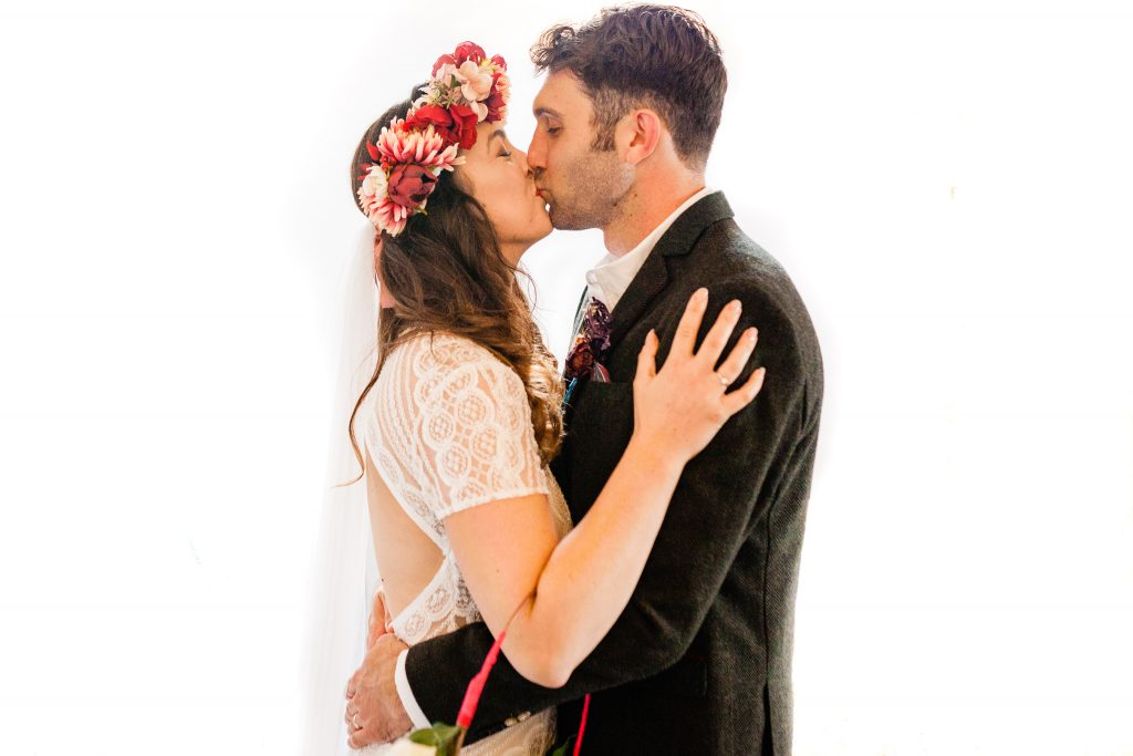 a bride and groom have their first kiss against a pure whit background. yorkshire festival wedding photography by emma and rich.