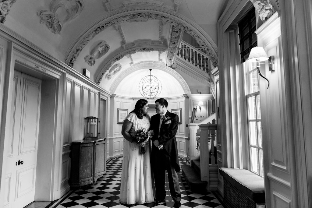 a bride and groom pose for a black and white wedding portrait in the hallway of barnett hill hotel. wedding photography by emma and rich