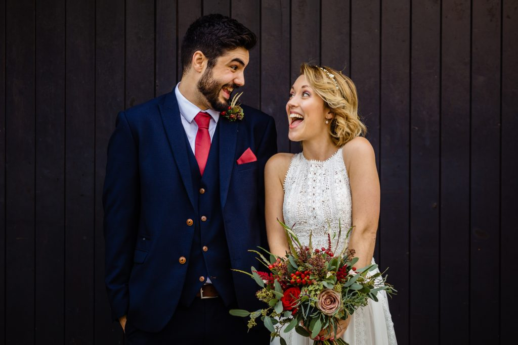 a bride and groom look at each other whilst laughing. manorial barn wedding photography by emma and rich