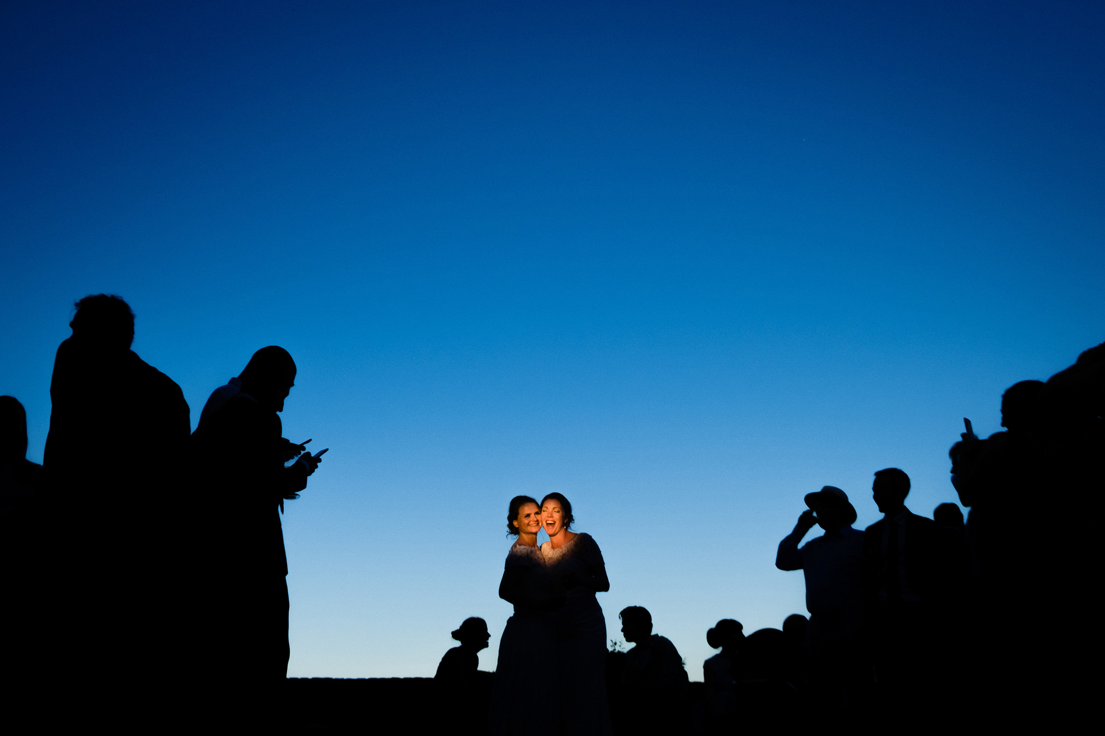 two brides, illuminated by a sunbeam, laugh as they are surrounded by their wedding guests in silhouette. image by the best wedding photographers of 2018, emma and rich