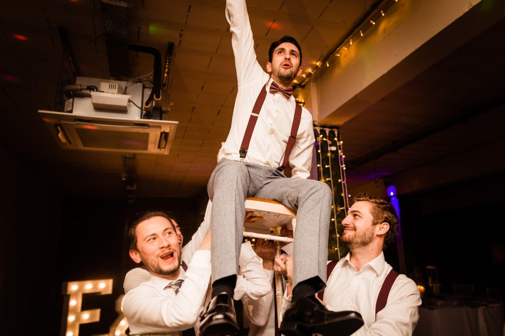 Jewish groom is lifted up in a chair by his friends. victoria warehouse, manchester, wedding photography by emma and rich.