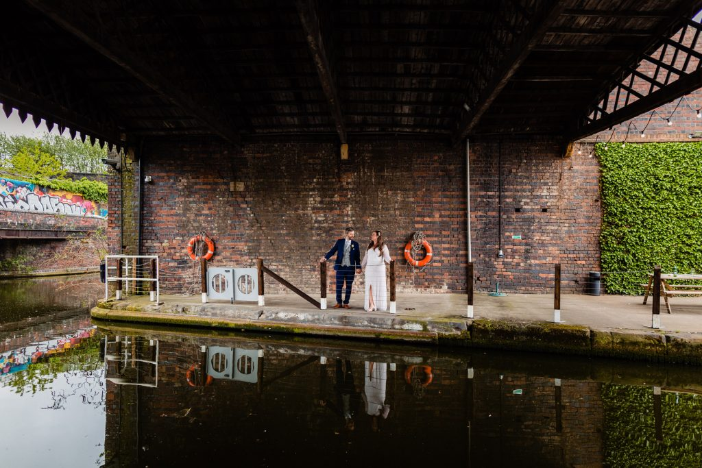 bride and groom by the canal at the bond company in birmingham by emma and rich fun wedding photographers