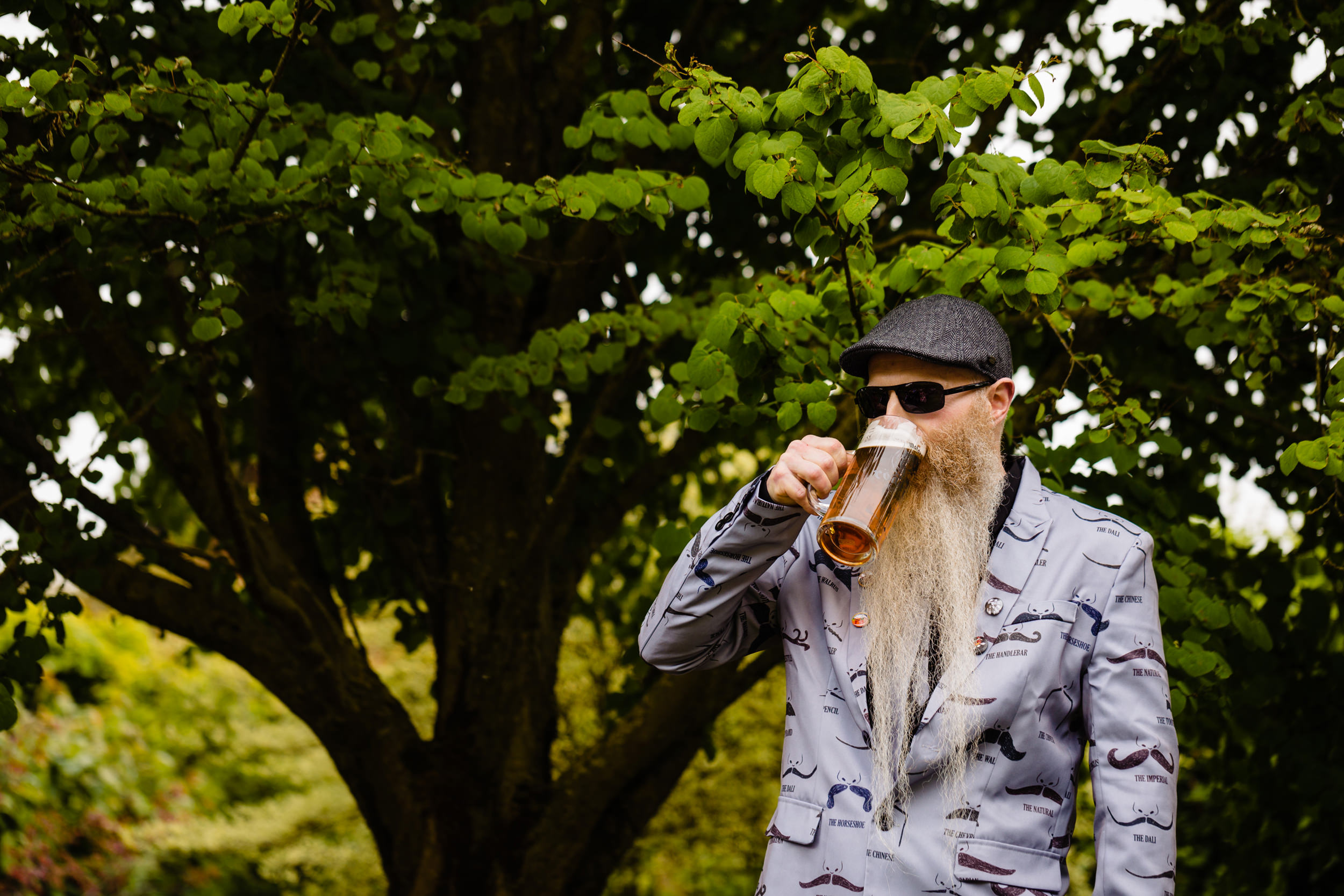 a groom drinks a pint as he waits for his bride to join him in the ceremony. wold top brewery wedding photography by emma and rich.