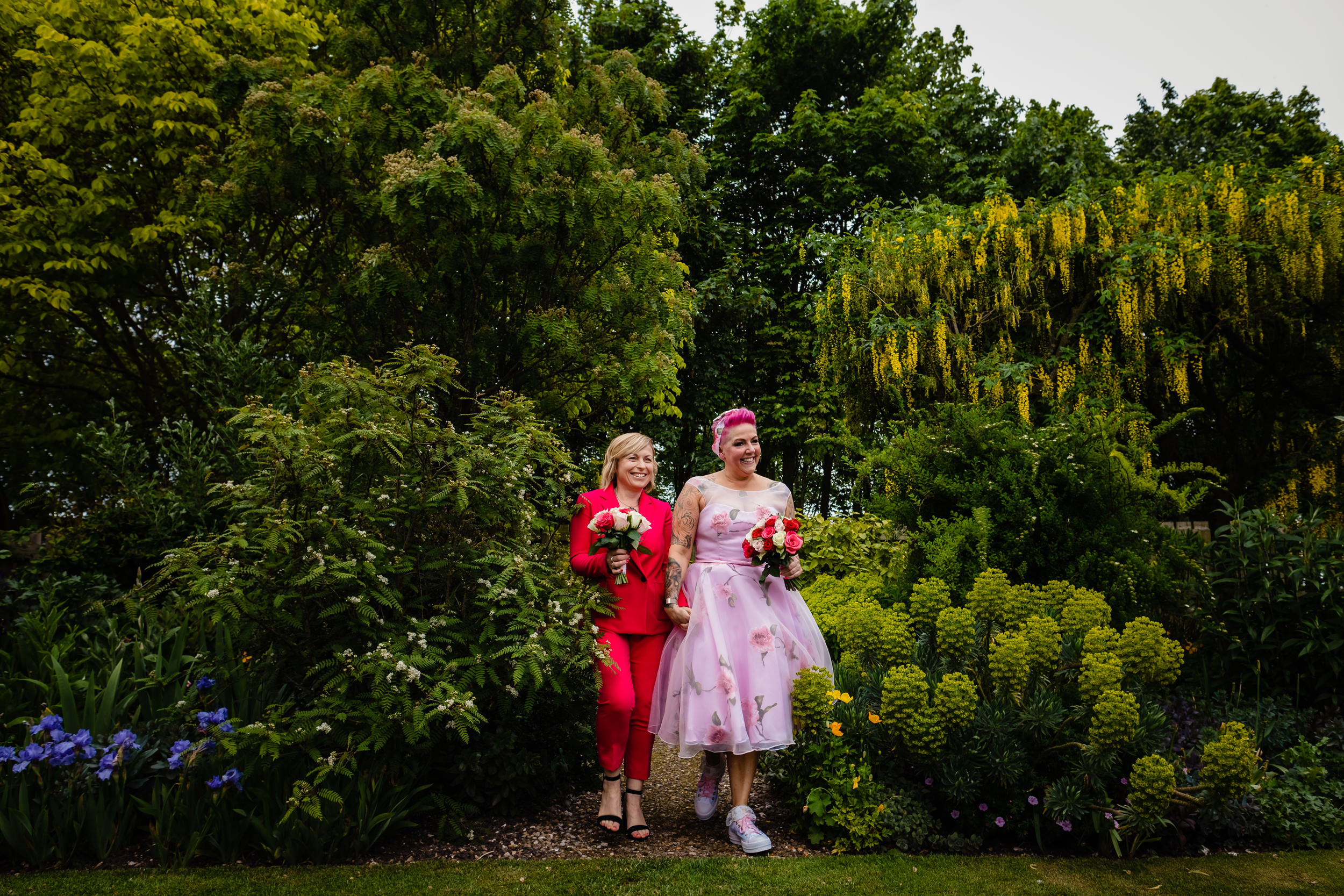 bride and bridesmaid walk through gardens to the wedding. wold top brewery wedding photography by emma and rich.