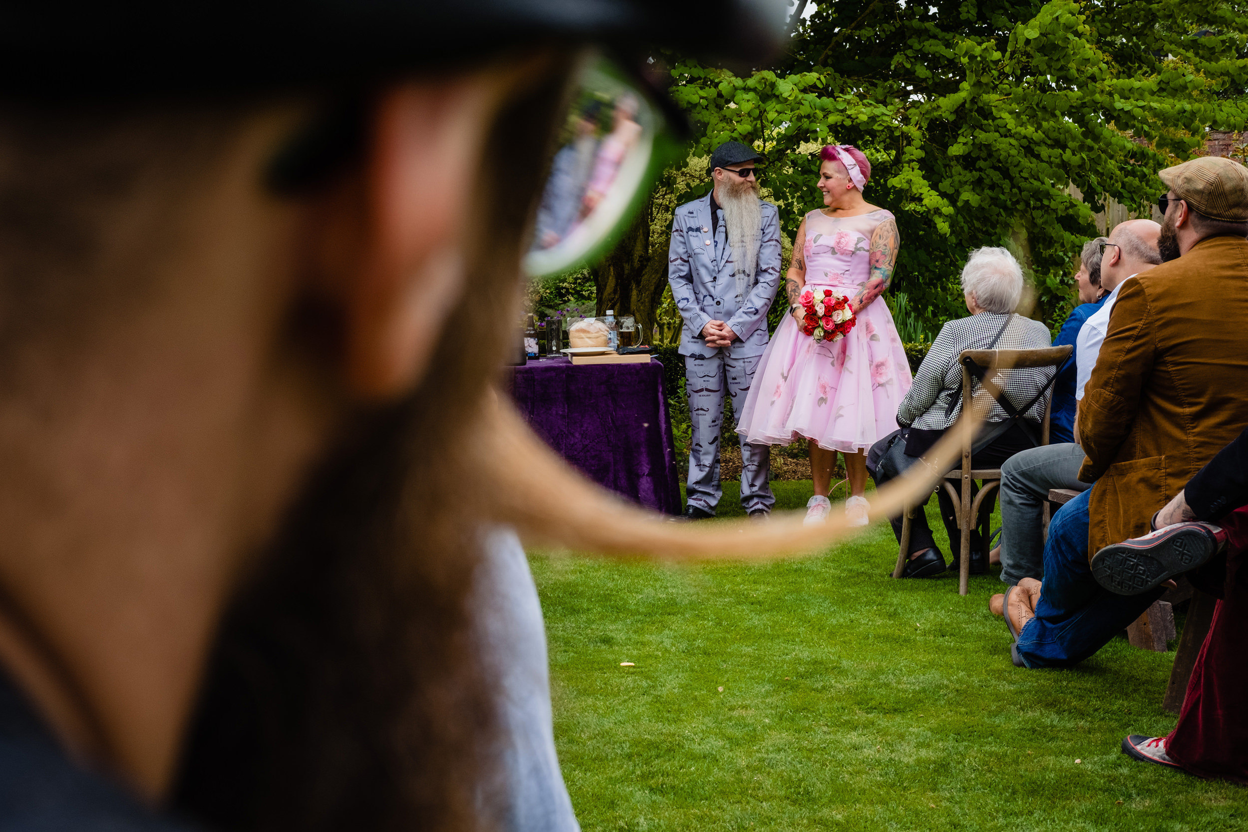 a man with a fantastic moustache watches a wedding. wold top brewery wedding photography by emma and rich.