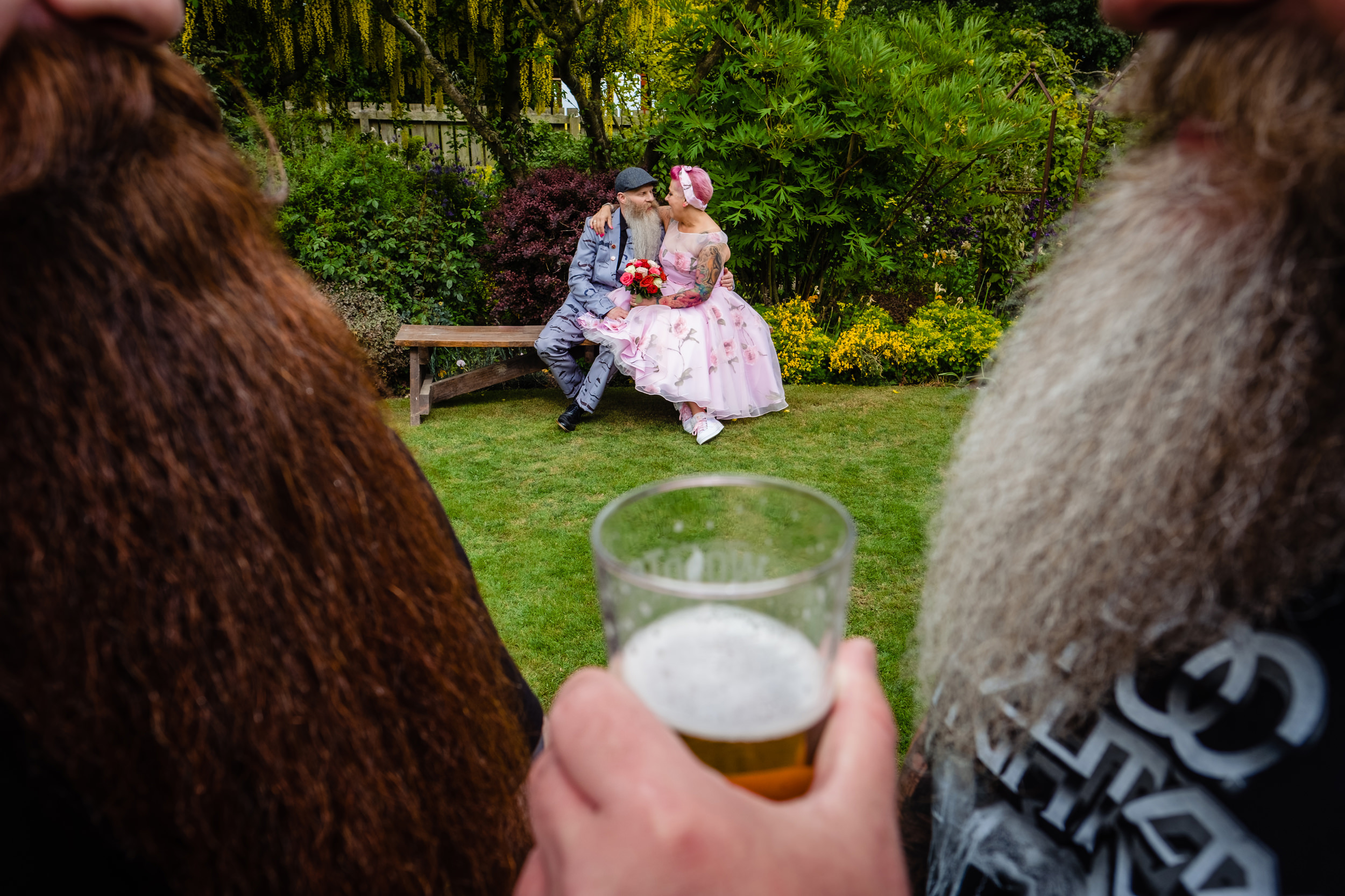 bride and groom cuddling in the garden framed by two massive beards. wold top brewery wedding photography by emma and rich.