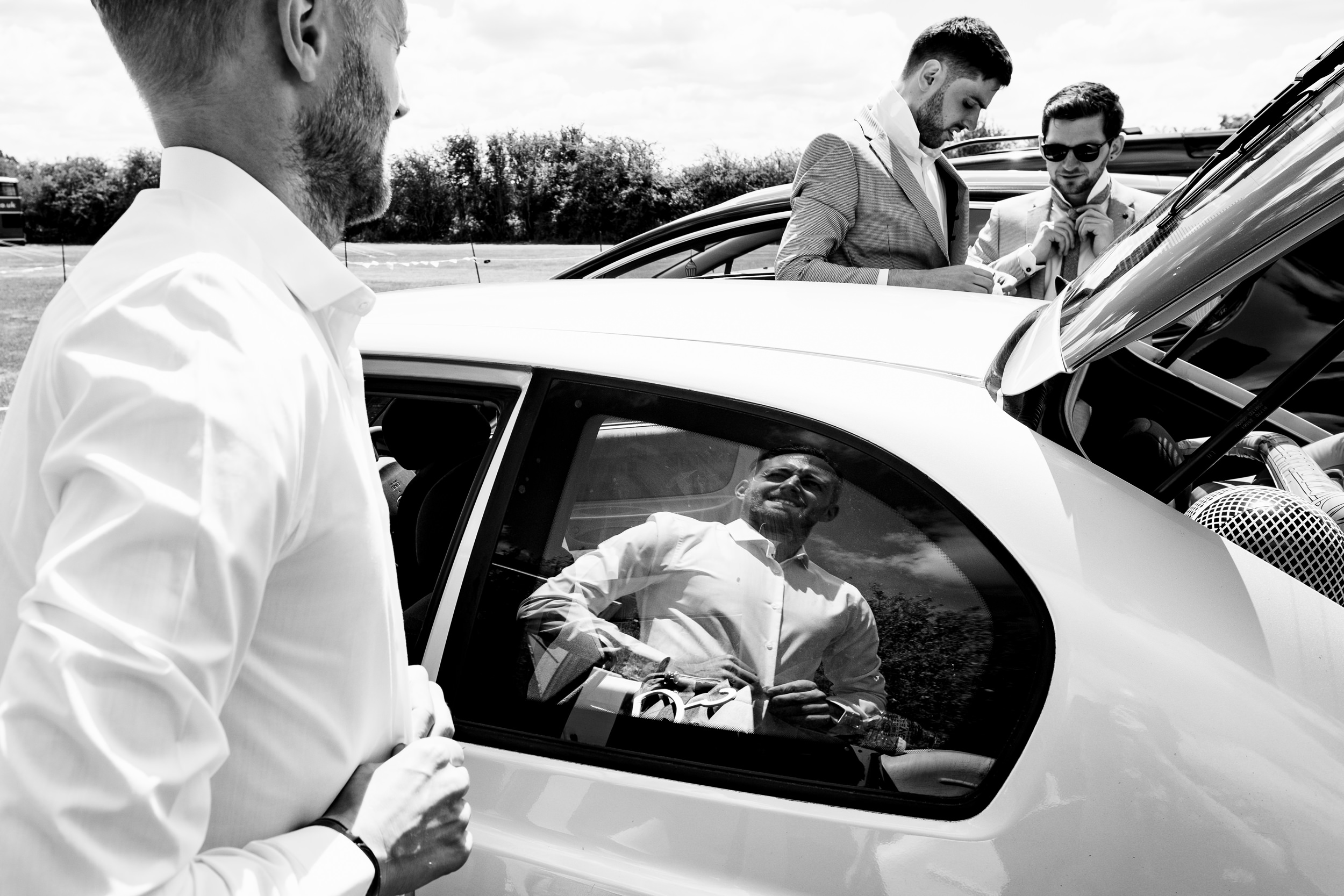 groom buttoning up his shirt in car park. maybush wedding co wedding photography by emma and rich.