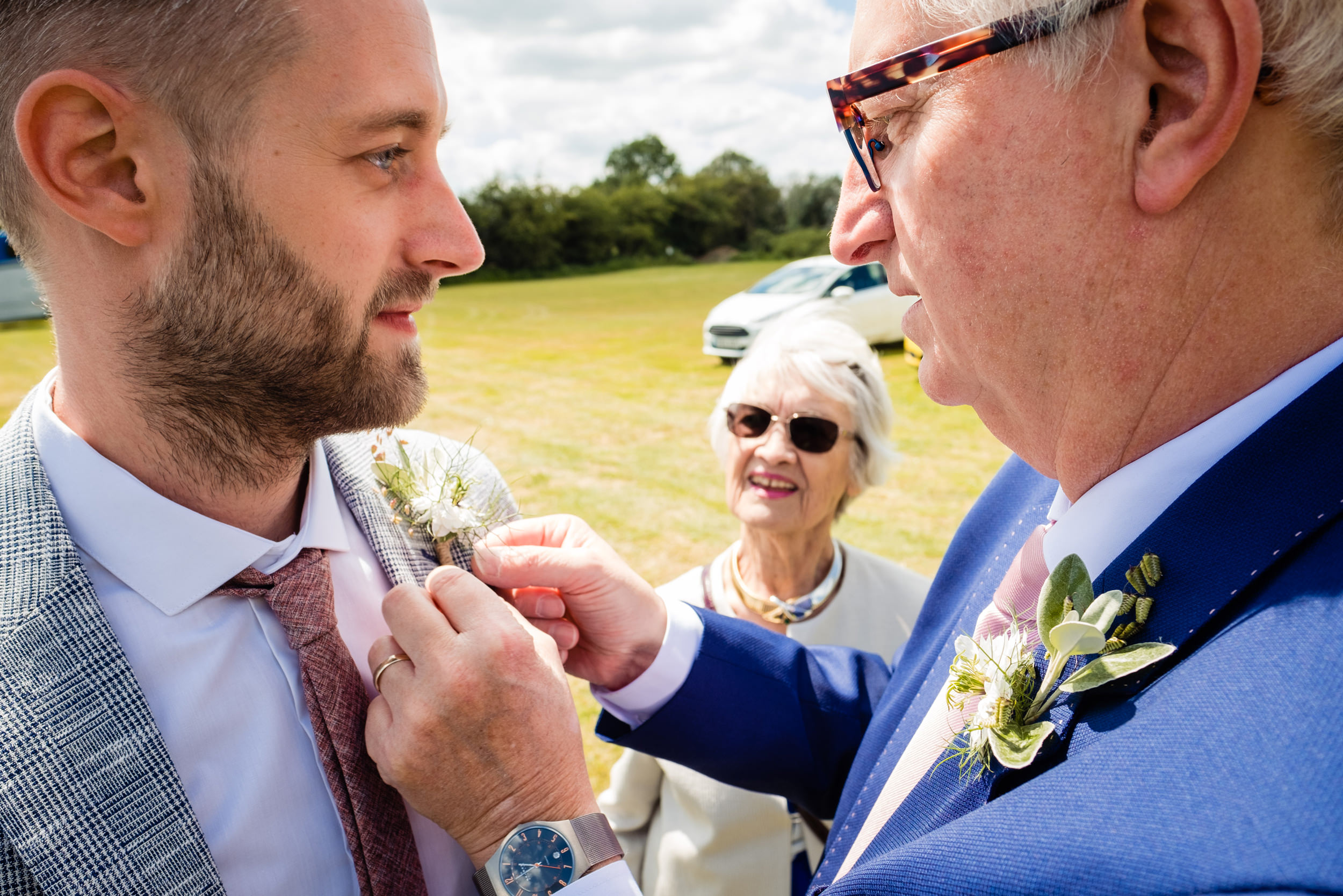 groom getting his buttonhole flower fixed by his dad. maybush wedding co wedding photography by emma and rich.