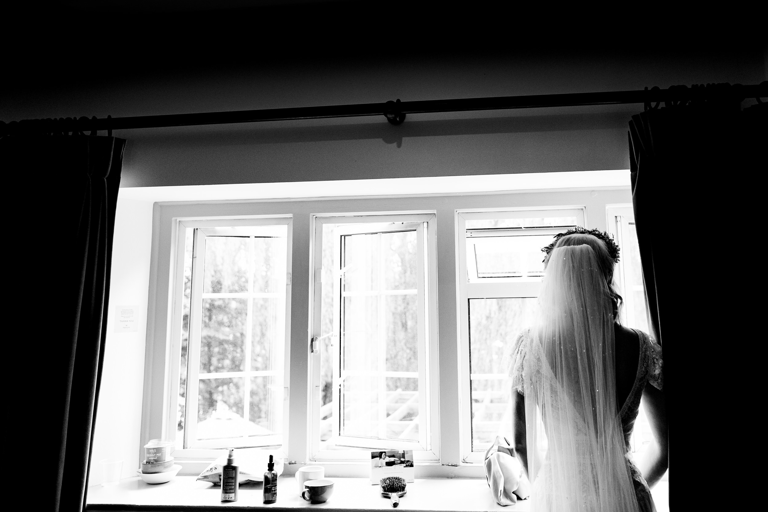 bride looking out of window. maybush wedding co wedding photography by emma and rich.