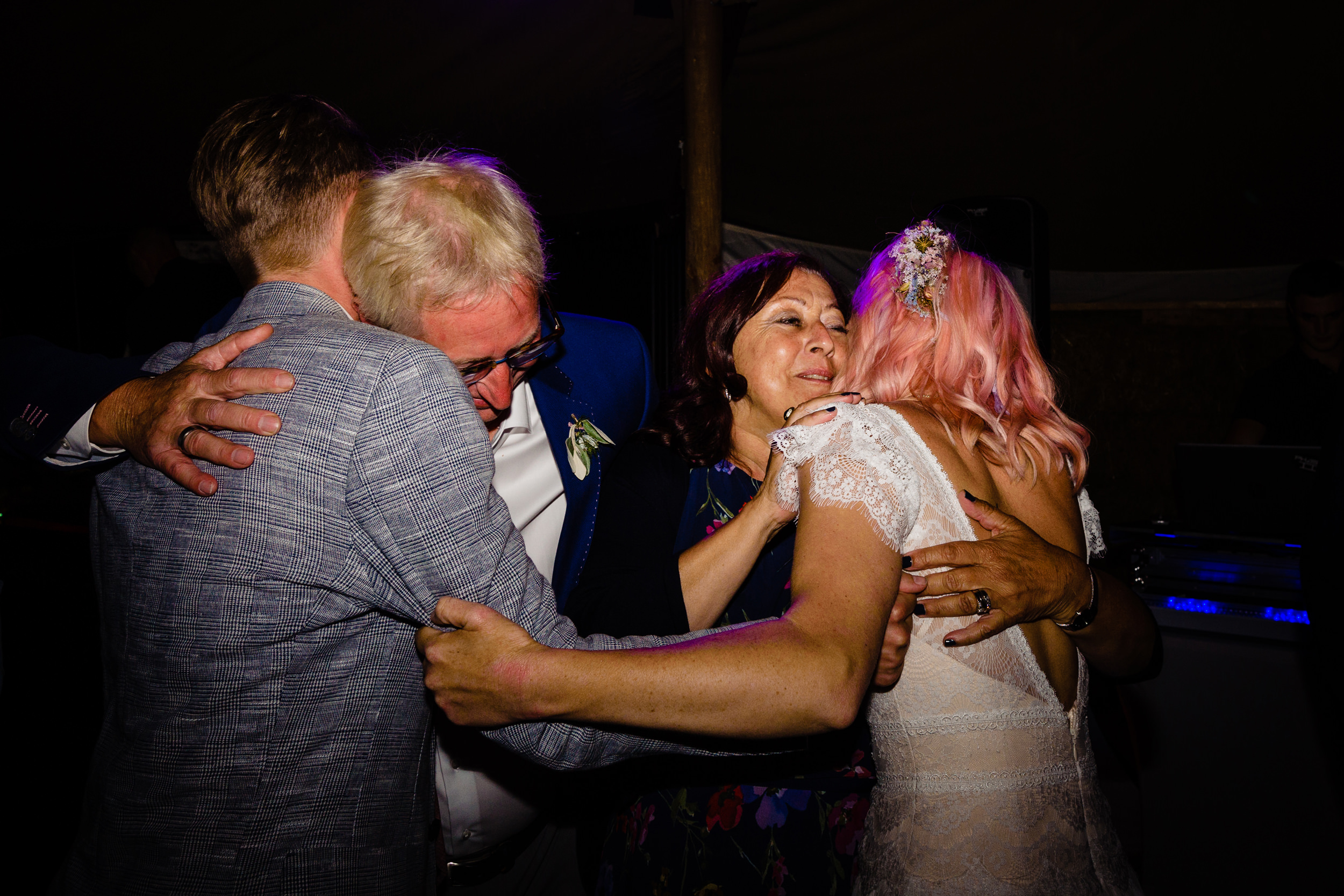 bride and groom hug parents on dancefloor. maybush wedding co wedding photography by emma and rich.