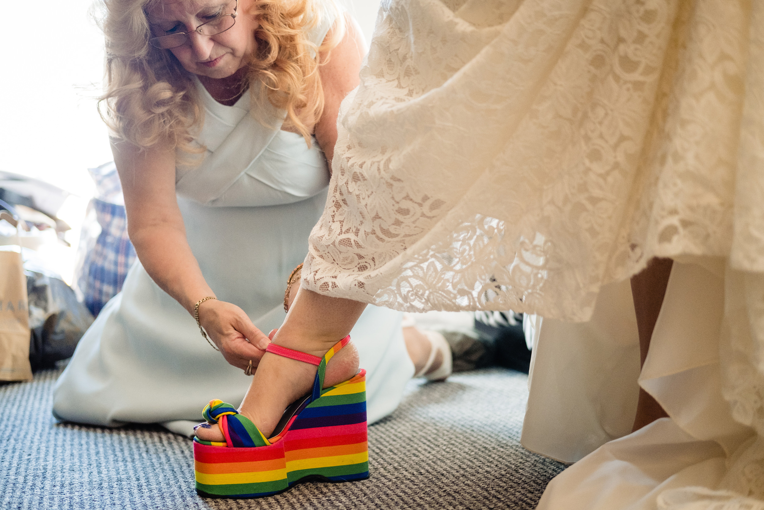 bride's mum helping bride put shoes on. plough inn, hathersage wedding photography by emma and rich.