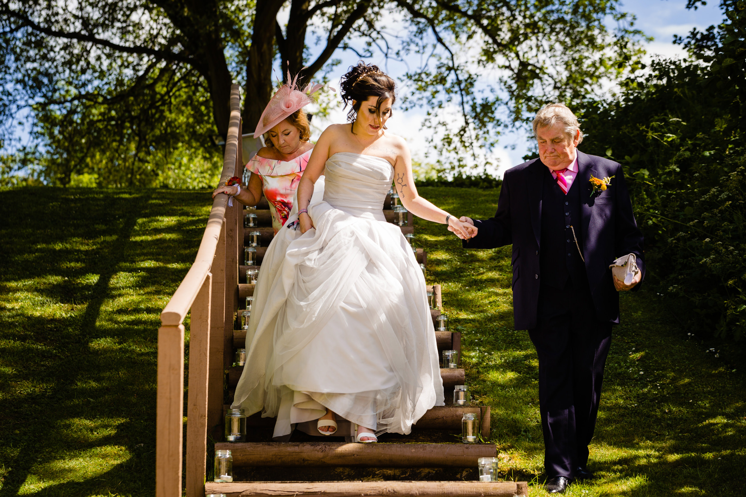 bride being helped down steps. plough inn, hathersage wedding photography by emma and rich.