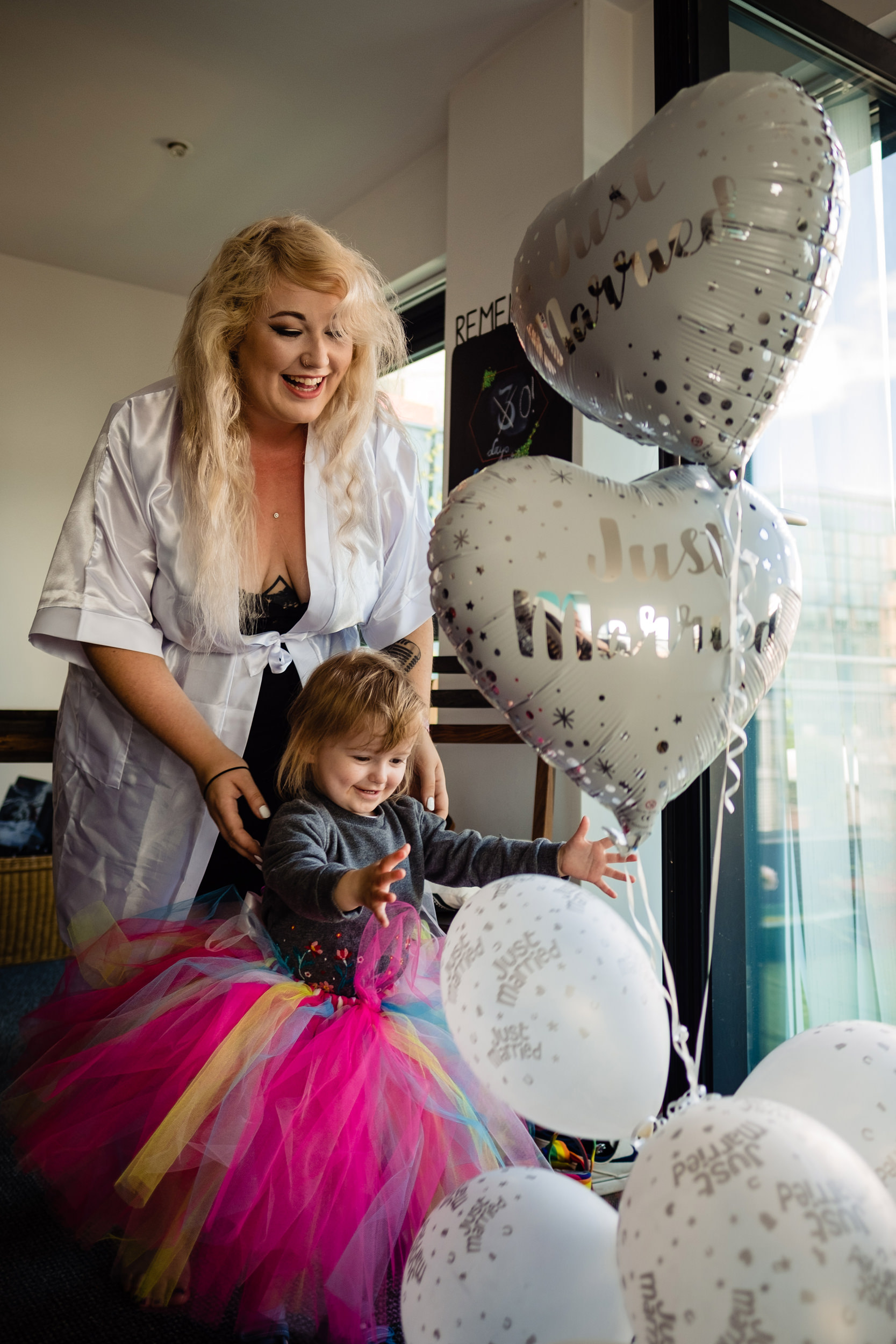 child in colourful tutu playing with wedding balloons. plough inn, hathersage wedding photography by emma and rich.