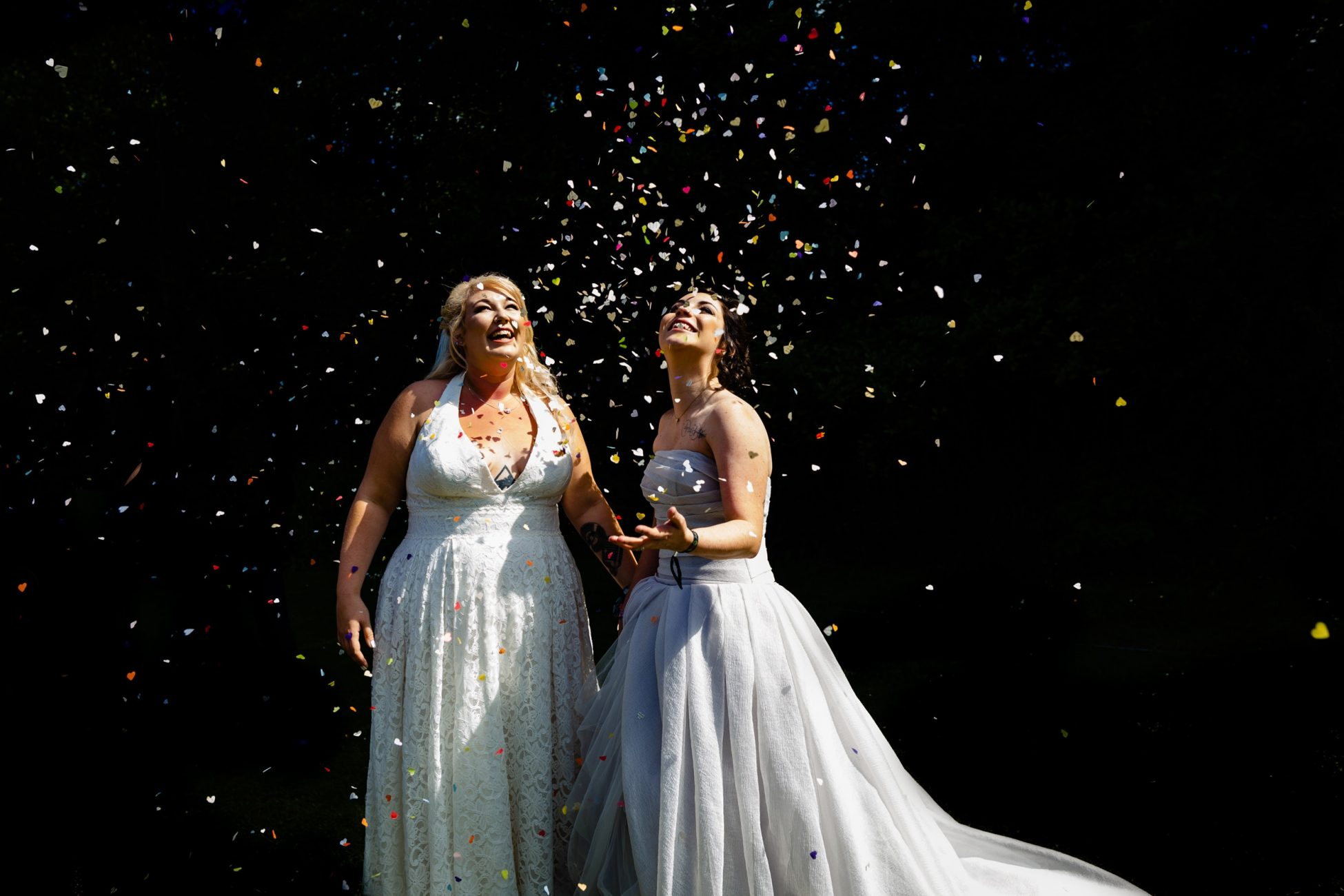 two brides stand in shower of confetti. plough inn, hathersage wedding photography by emma and rich.