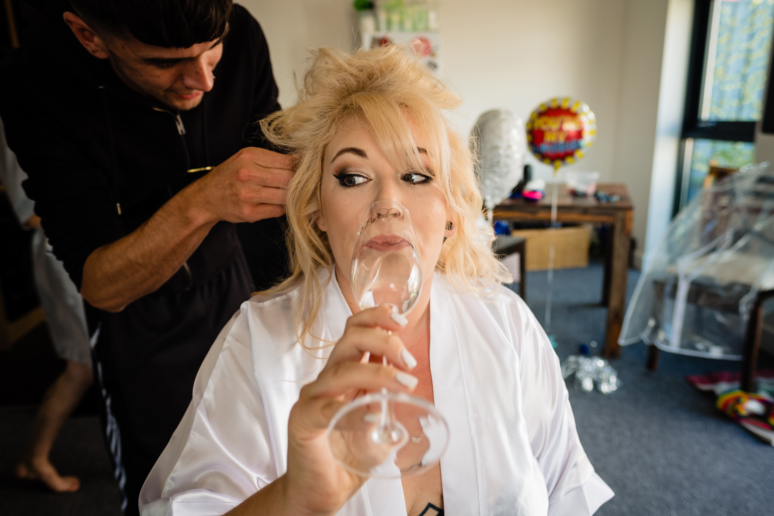 bride sipping champagne as she has her hair done. plough inn, hathersage wedding photography by emma and rich.