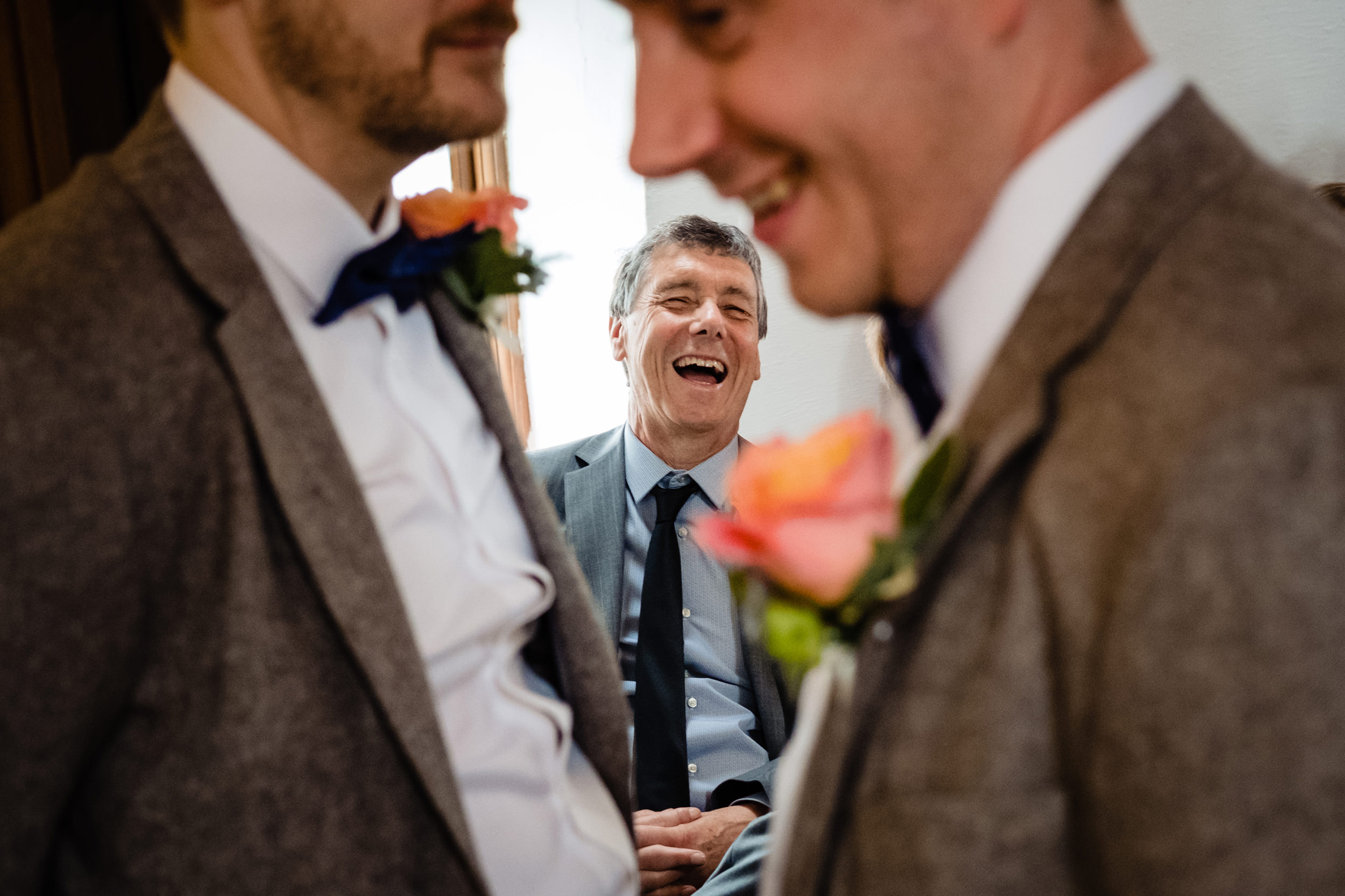 grooms father laughs at him before the ceremony. wildwood and eden wedding photography by emma and rich.