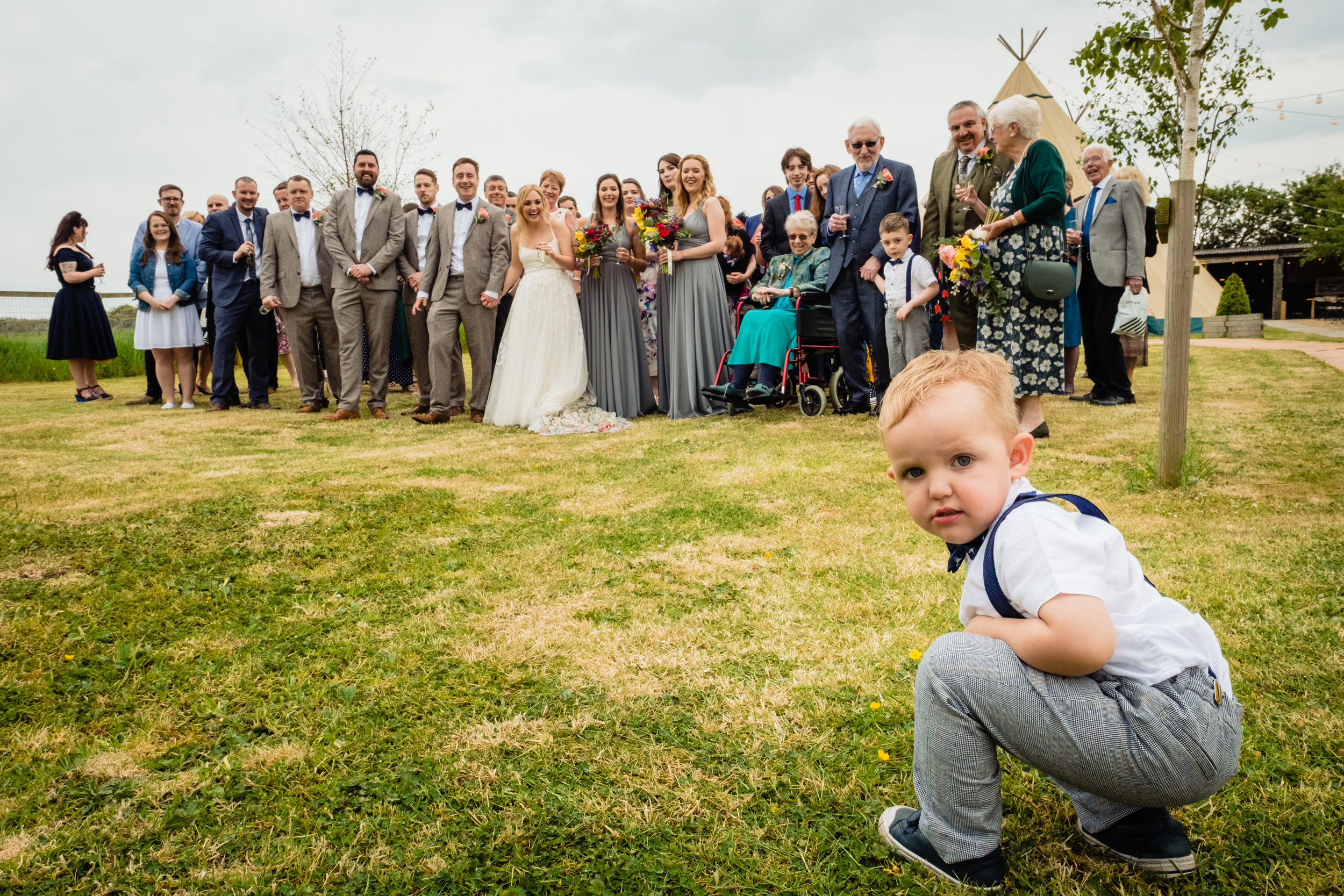 toddler refusing to get in group shot at wedding. wildwood and eden wedding photography by emma and rich.