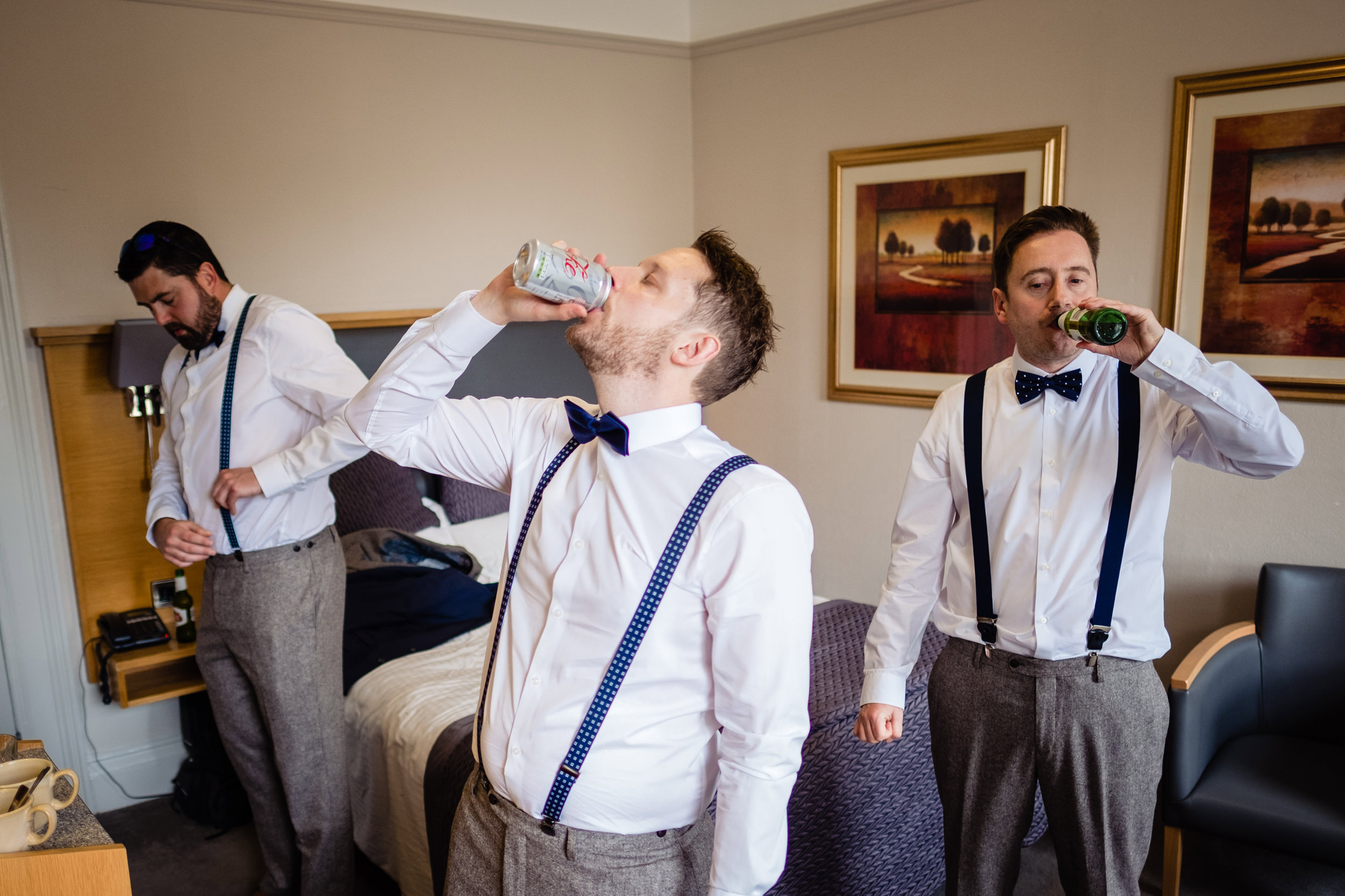 groom and ushers having a beer whilst getting ready. wildwood and eden wedding photography by emma and rich.