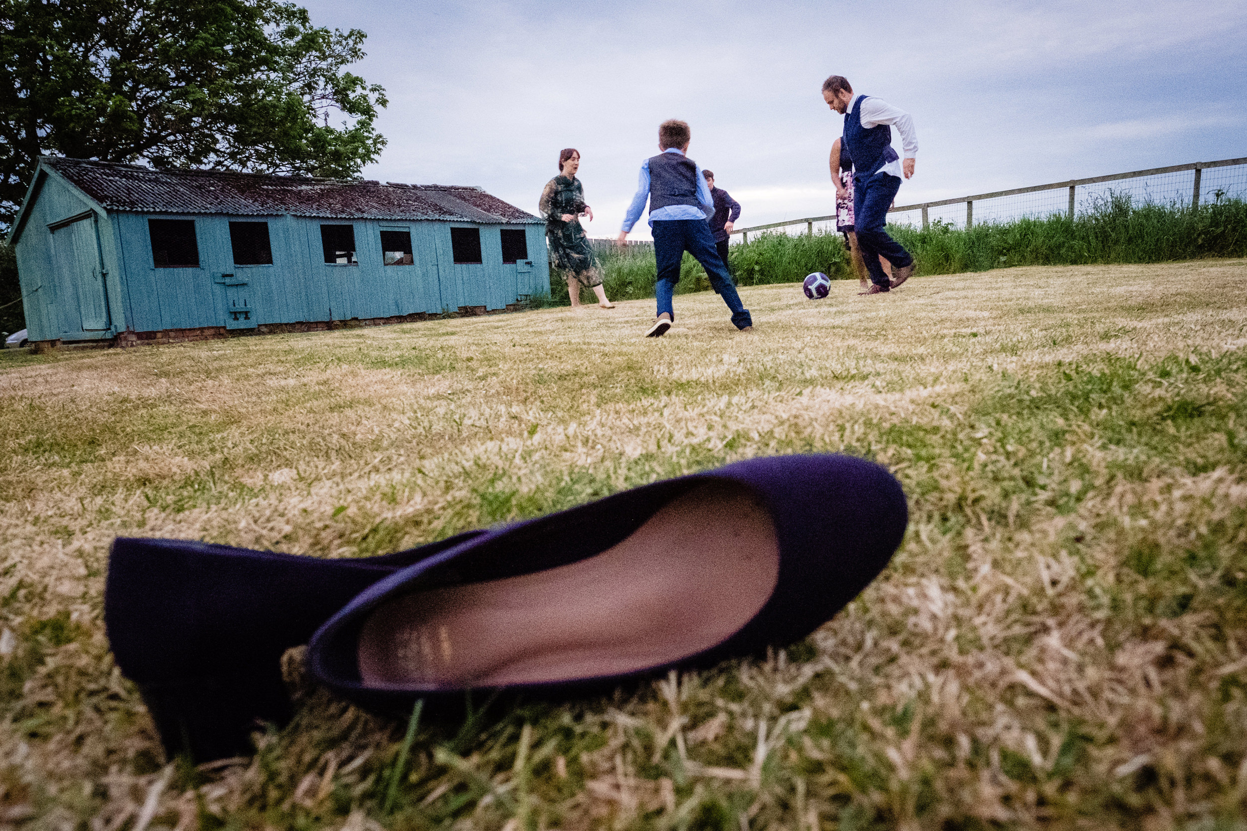 wedding guests playing football. wildwood and eden wedding photography by emma and rich.
