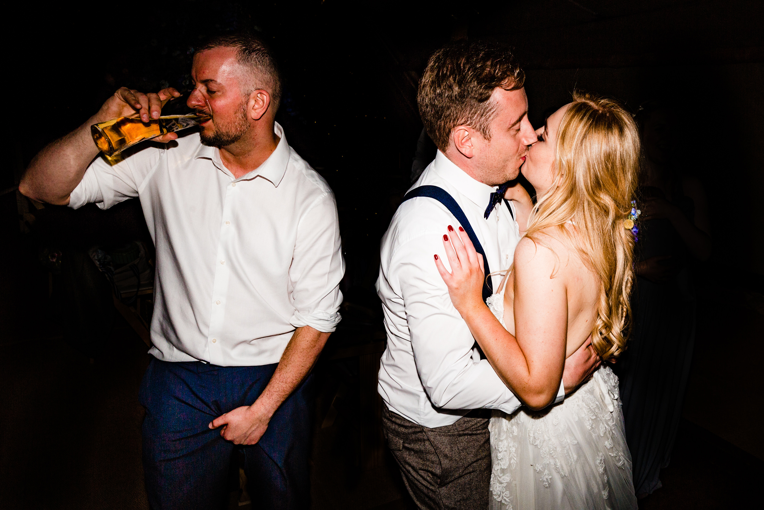 guest drinks beer next to newlyweds. wildwood and eden wedding photography by emma and rich.