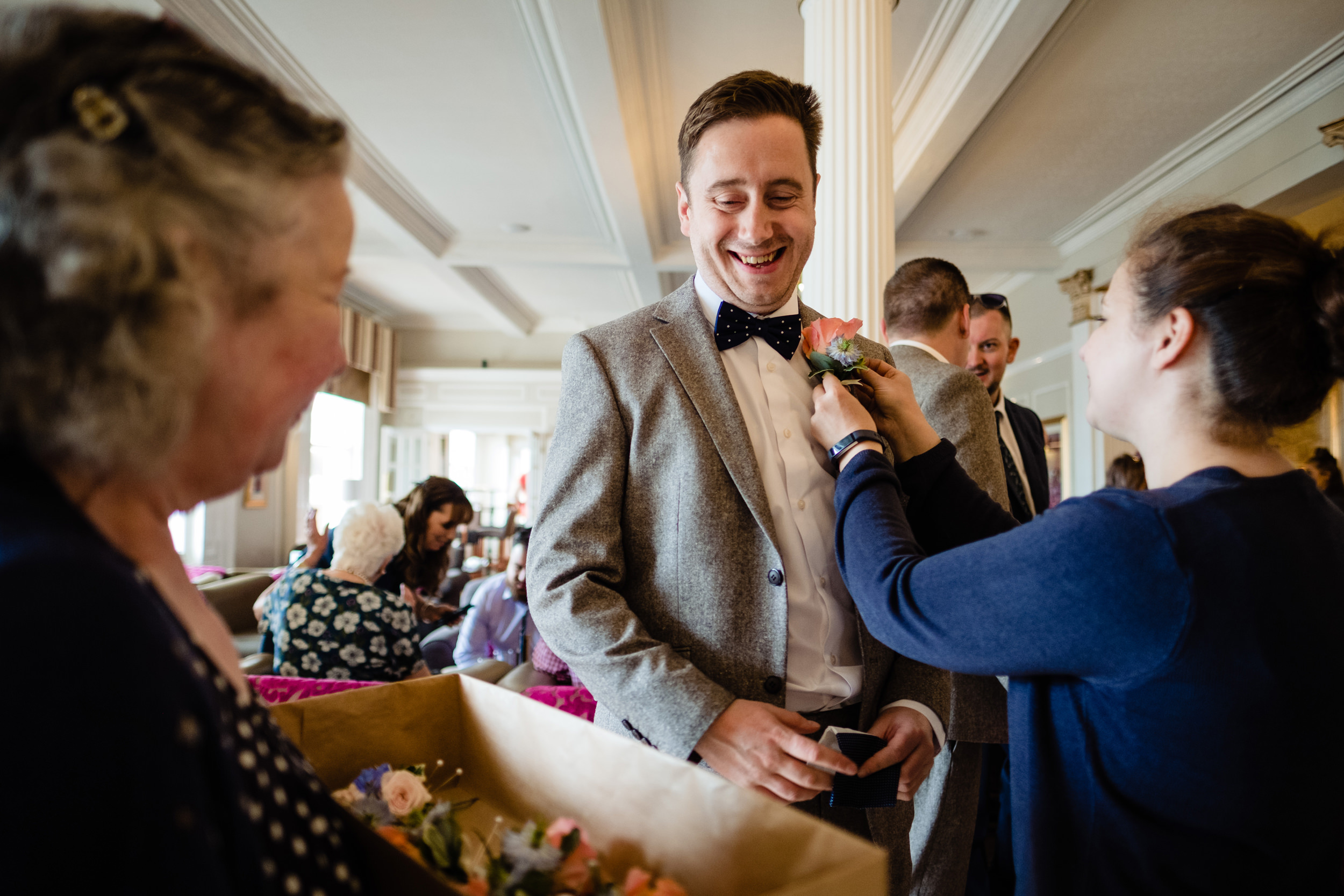 groom getting his buttonhole flower fitted. wildwood and eden wedding photography by emma and rich.