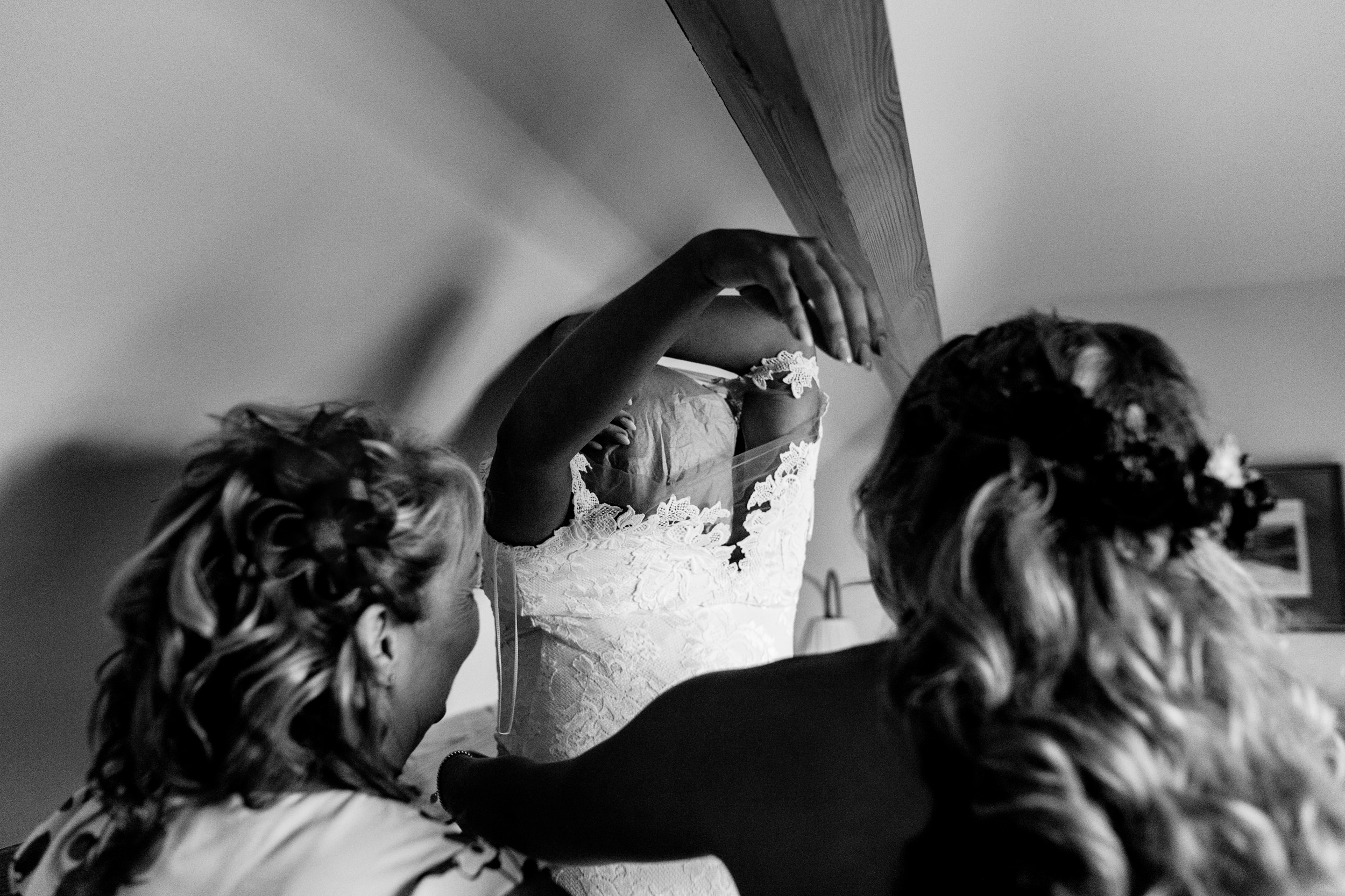 bride putting on her dress. esk valley wedding photography by emma and rich.