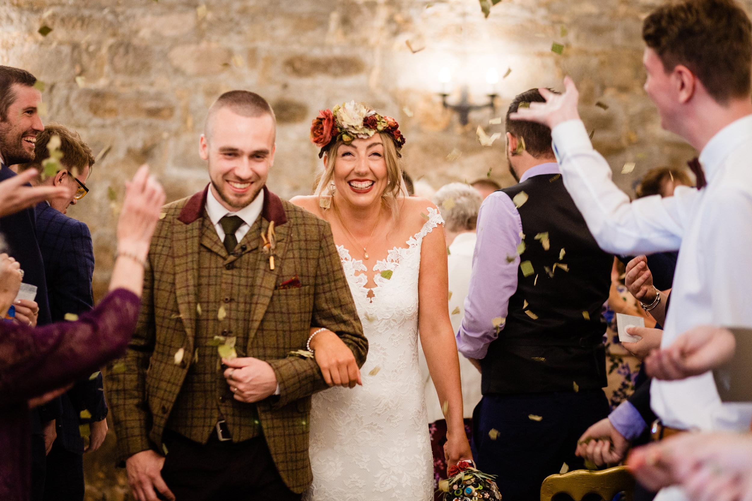 newlyweds walk through confetti. esk valley wedding photography by emma and rich.