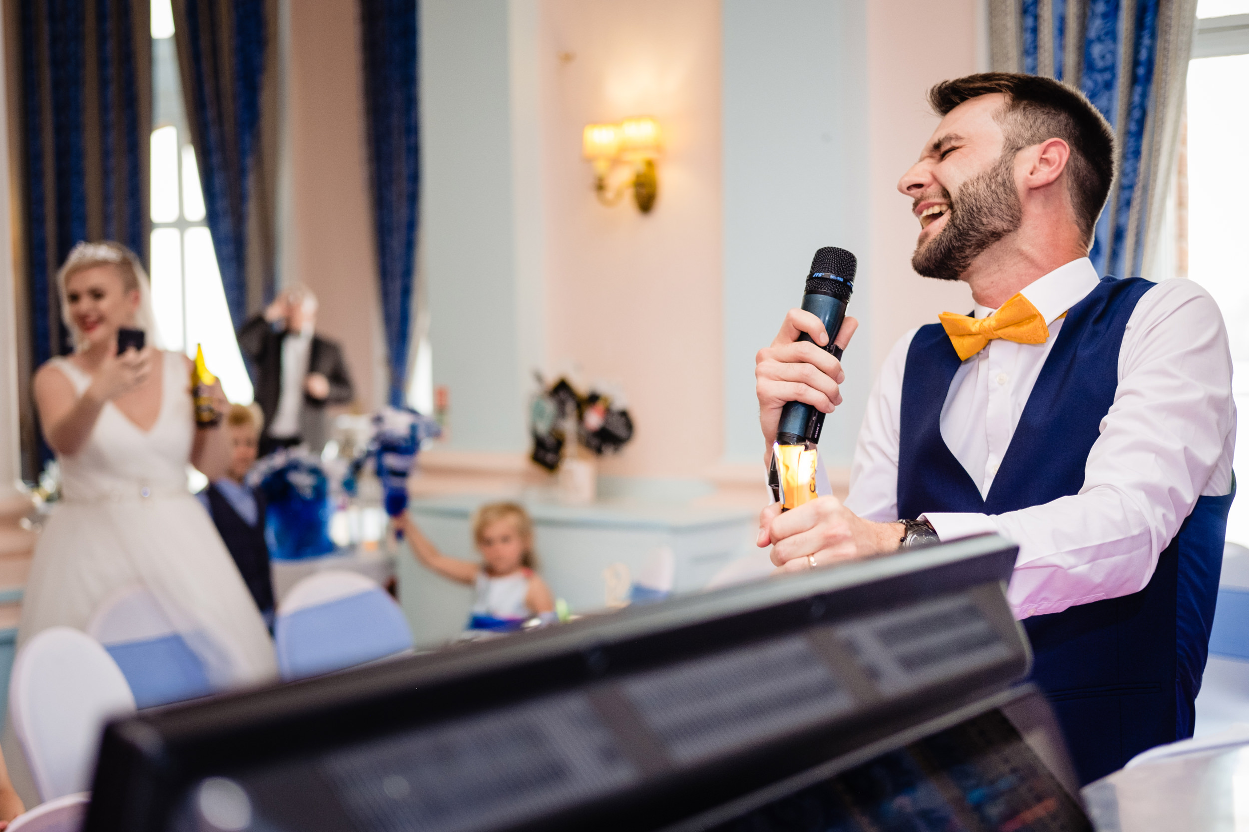 groom singing karaoke. grand hotel scarborough wedding photography by emma and rich.