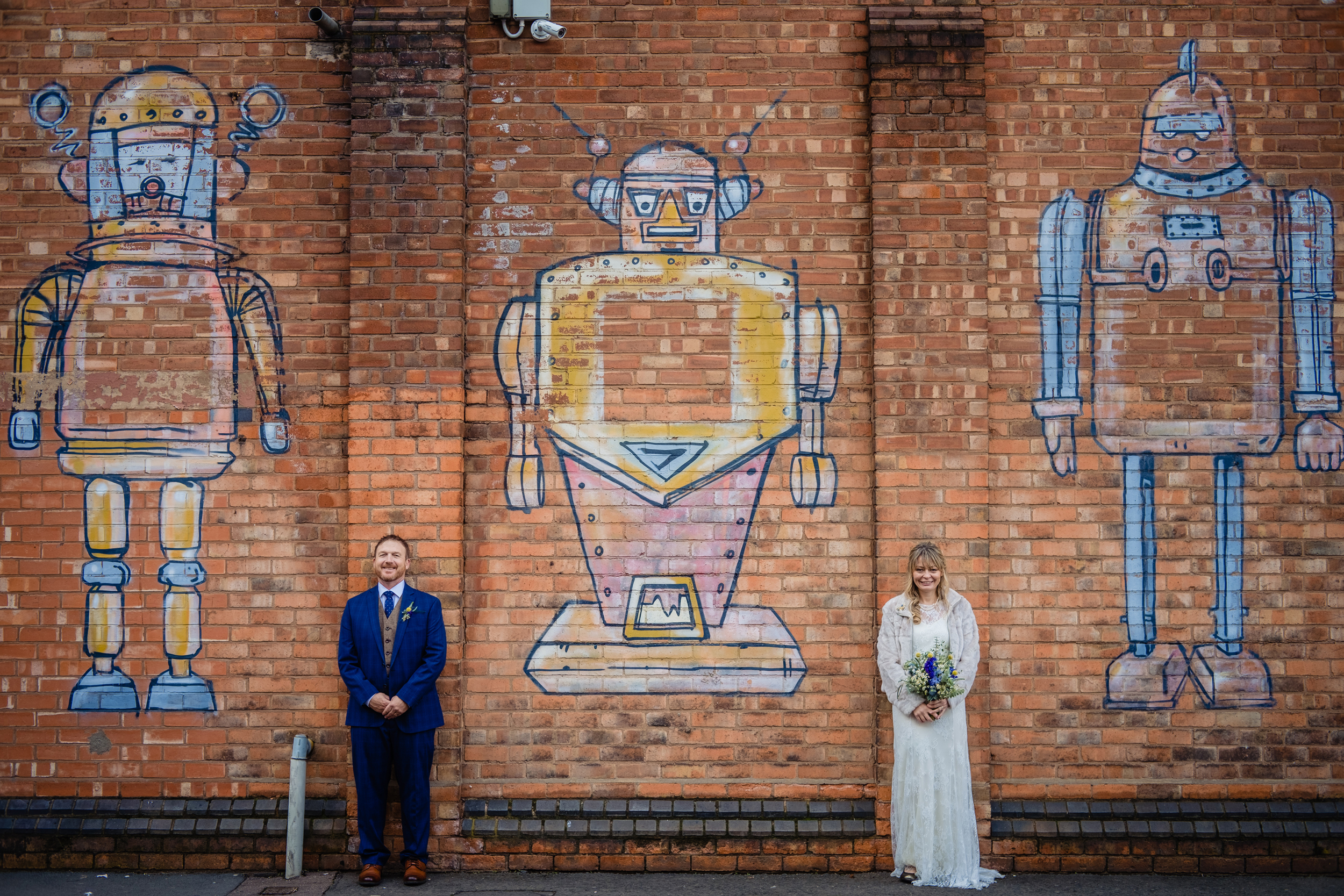 bride and groom pose for pictures in front of graffiti. birmingham wedding photography by emma and rich.