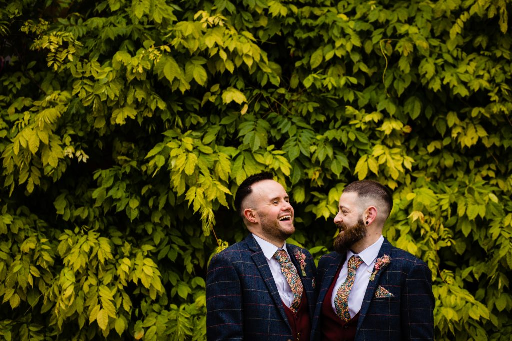 two grooms pictured in front of ivy. ettington park hotel wedding photography by emma and rich.