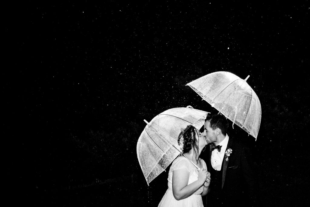 newlywed couple kissing in the rain with umbrellas - the cowshed at woodall farm wedding photography by emma and rich